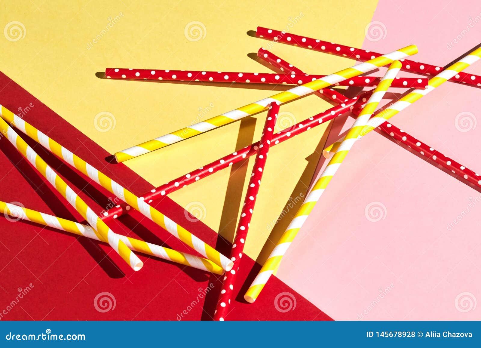Palhas bebendo plásticas coloridas isoladas sobre o rosa, fundo amarelo, vermelho