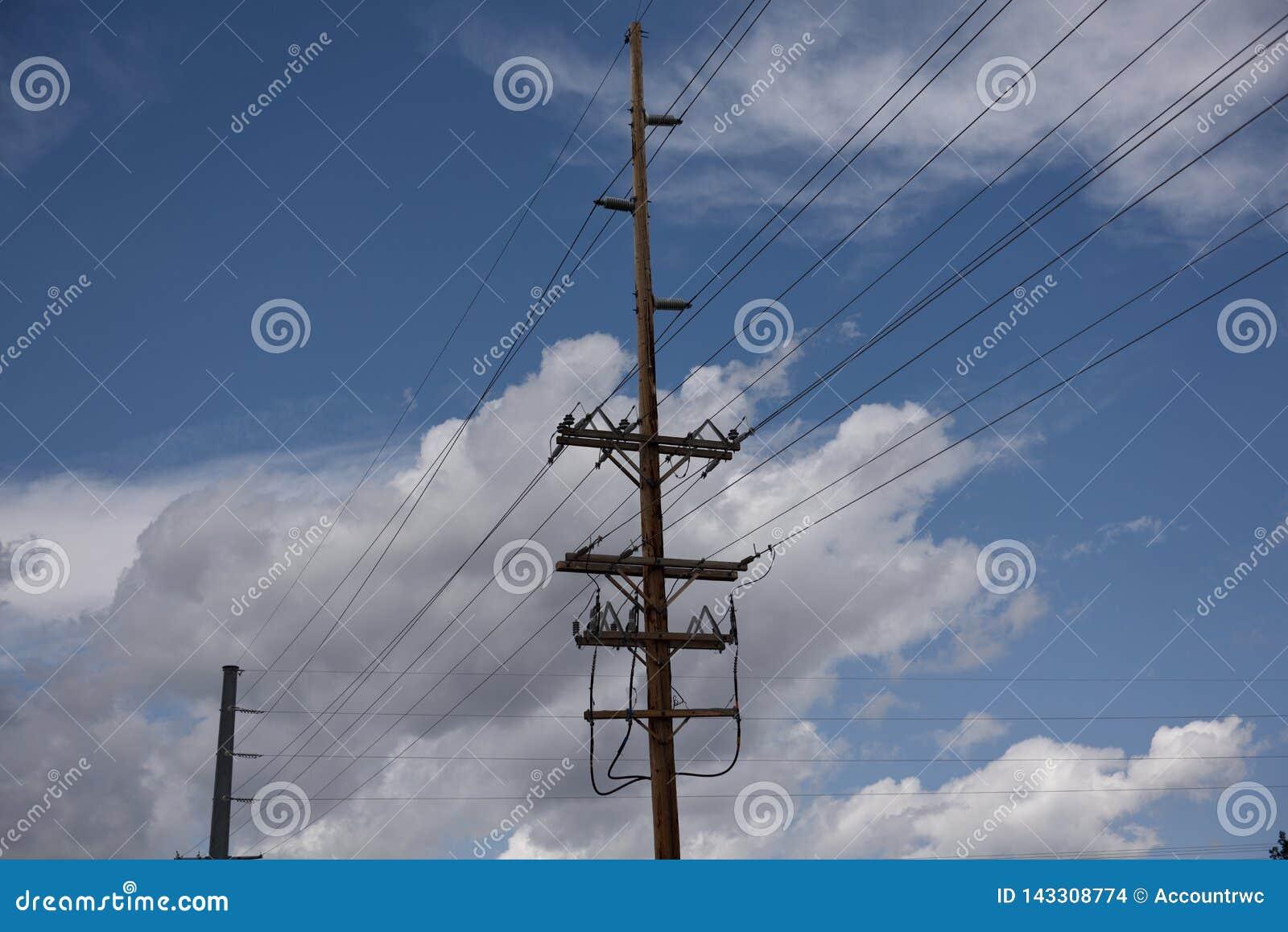 Pali pratici elettrici e linee elettriche ad alta tensione sopraelevate contro un cielo blu e le nuvole