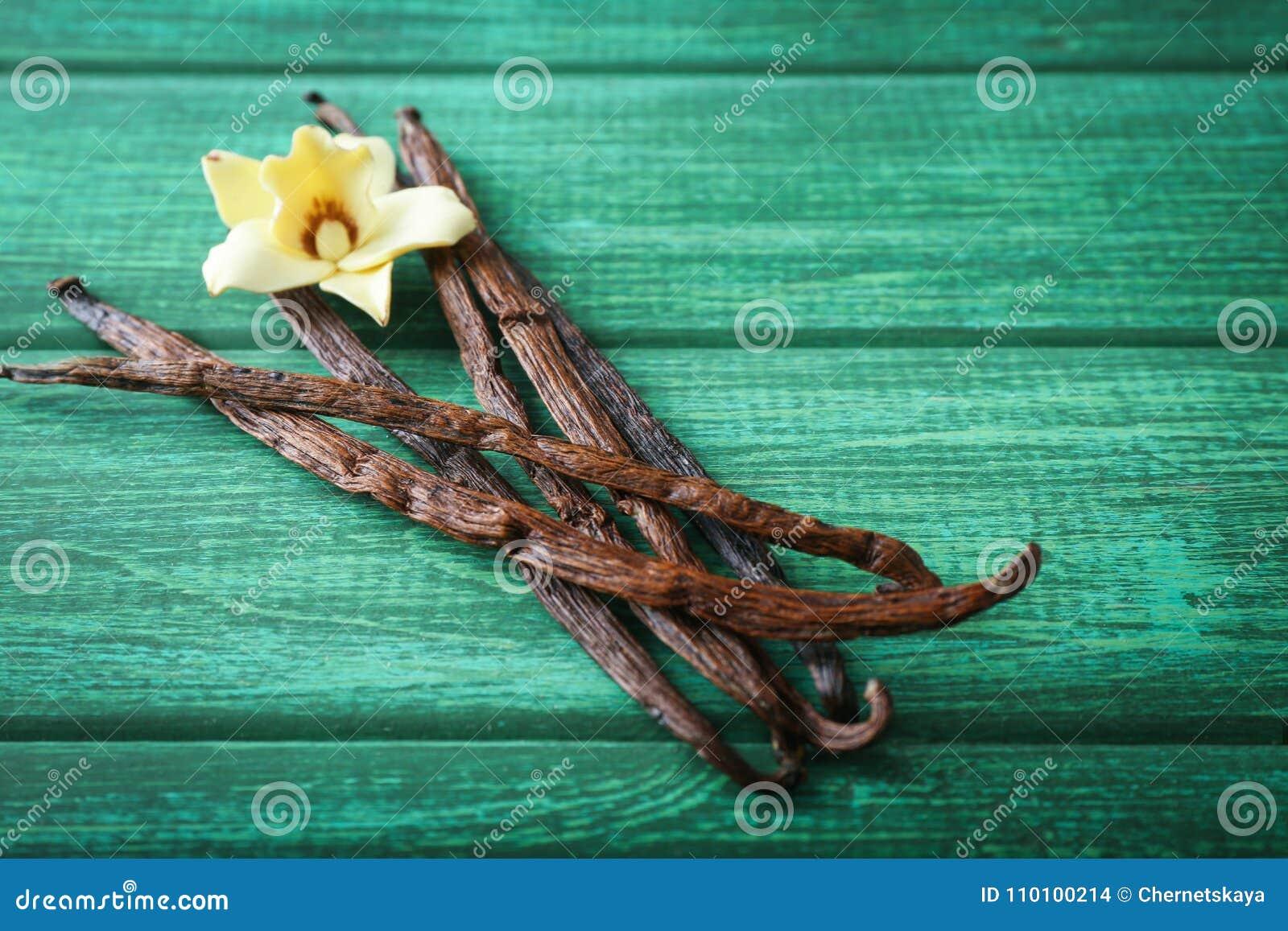Palillos y flor de la vainilla en fondo