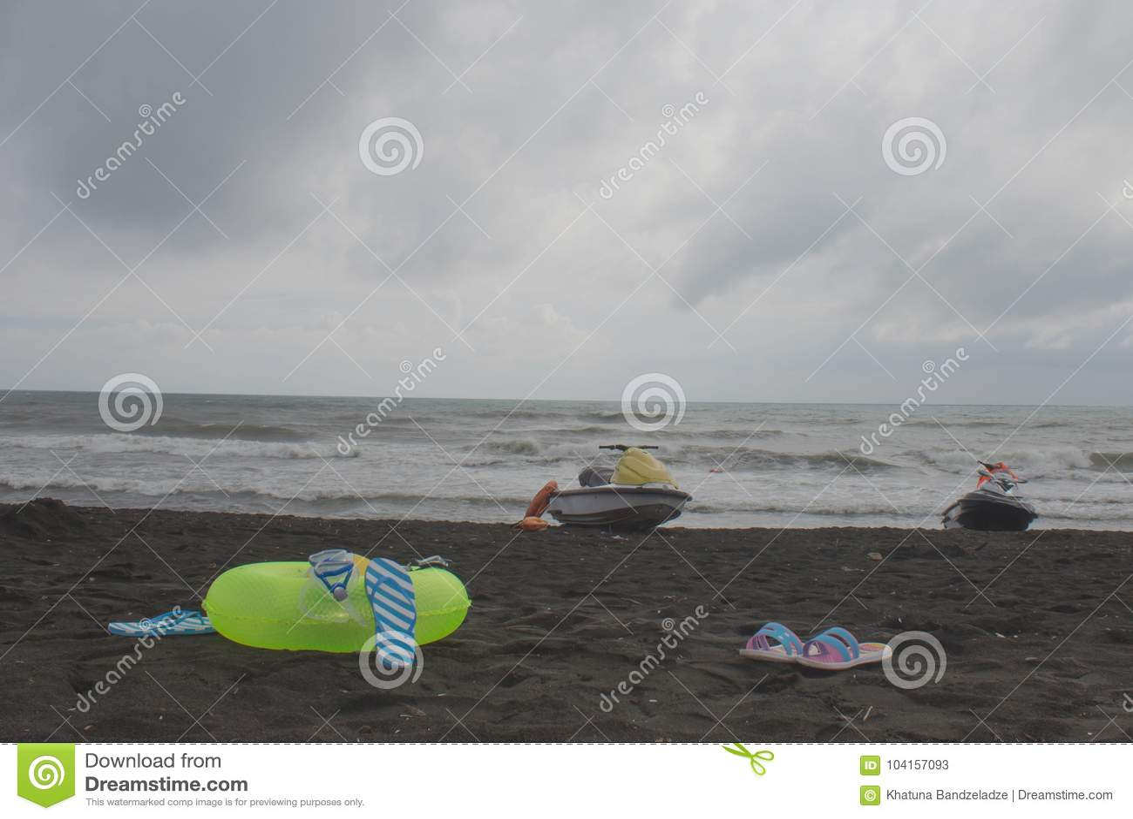 Palla, vetri di nuoto, sandalo, acquascooter ed anello di galleggiamento sulla spiaggia annuvolamento, impulso