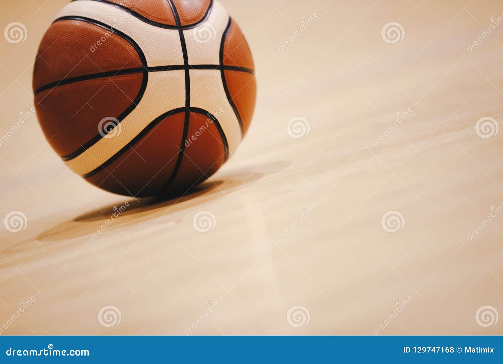 Pallacanestro sulla fine di legno del pavimento della corte su con l arena vaga nel fondo