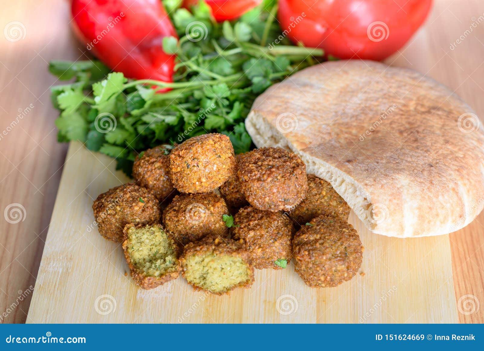 Palle del Falafel, peperone dolce, pane pita-arabo e prezzemolo fresco verde su fondo rustico di legno