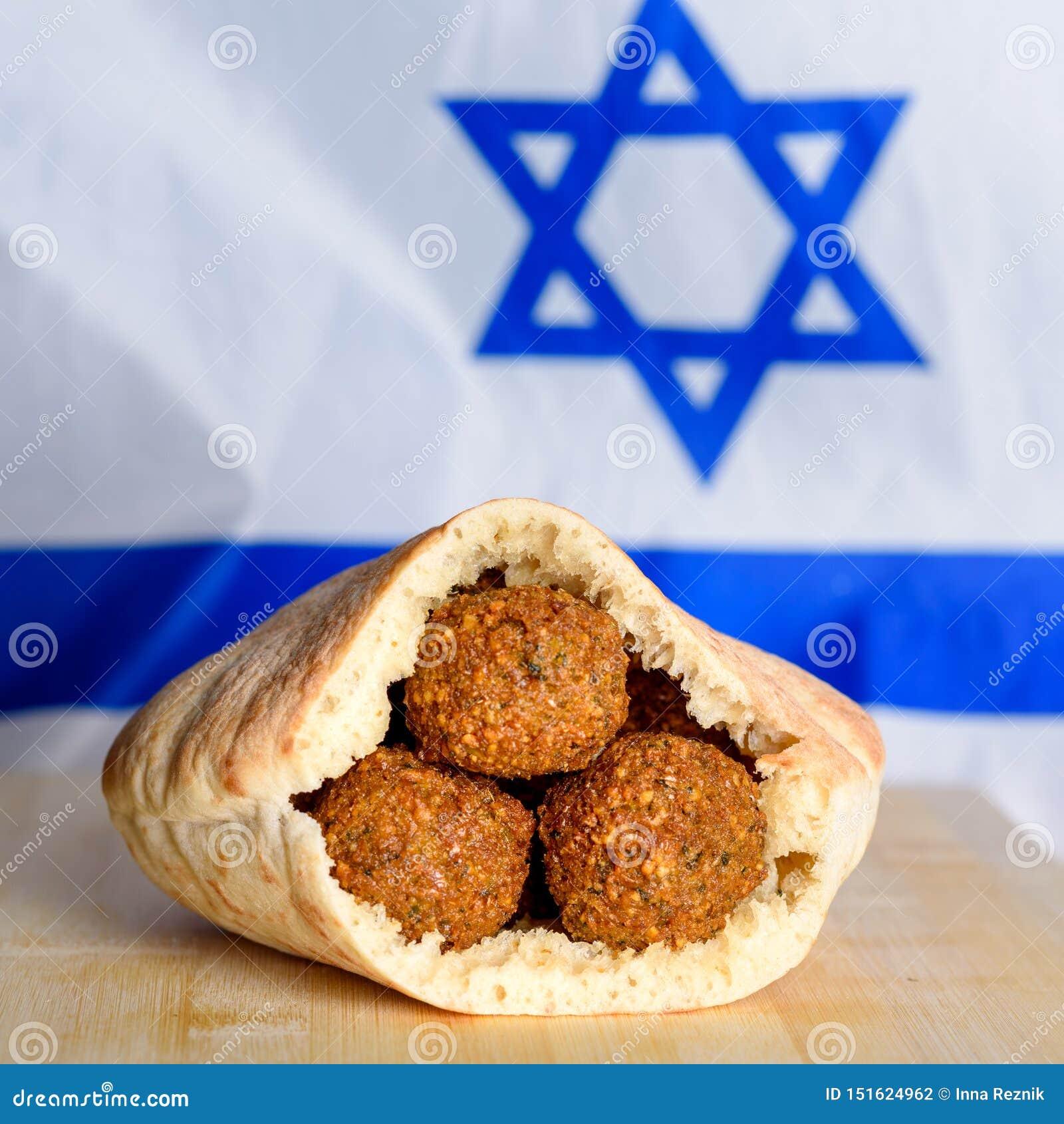 Palle del Falafel in una pita sul fondo di legno della bandiera di Israele della tavola
