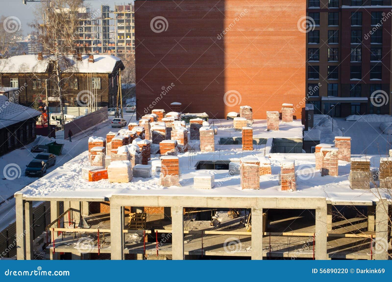 Pallet della costruzione di inverno dei mattoni nel centro urbano