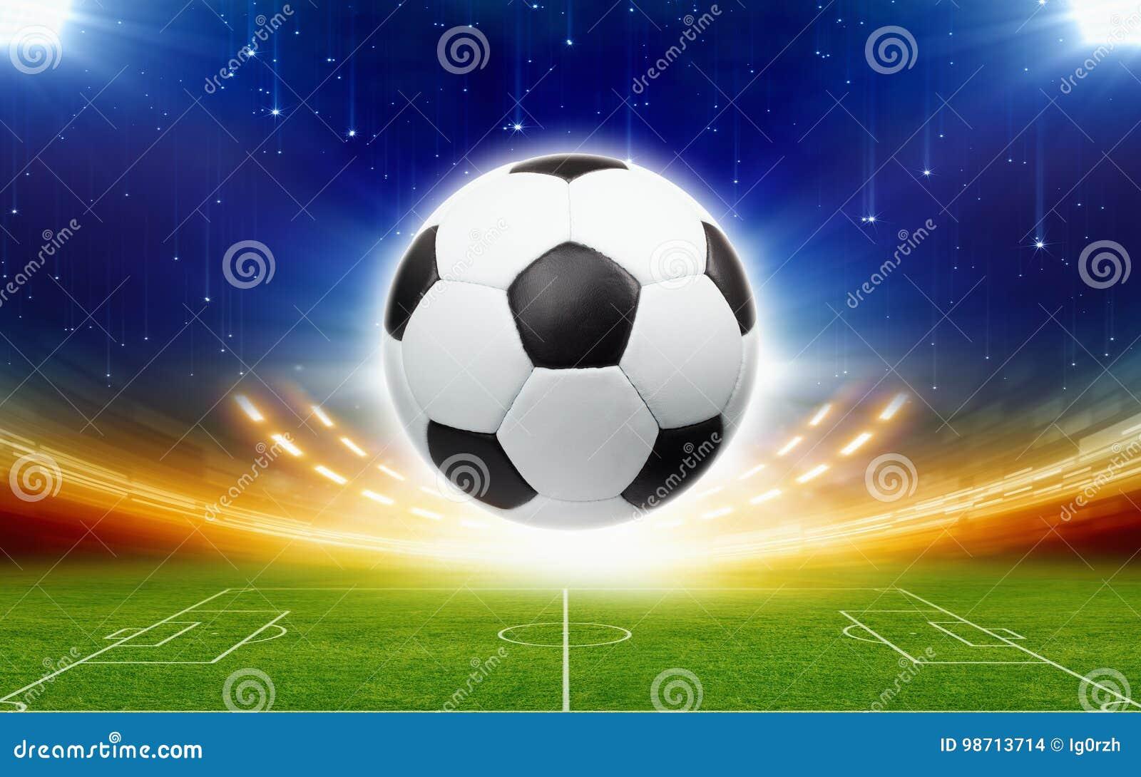 Pallone da calcio sopra stadio di football americano verde alla notte