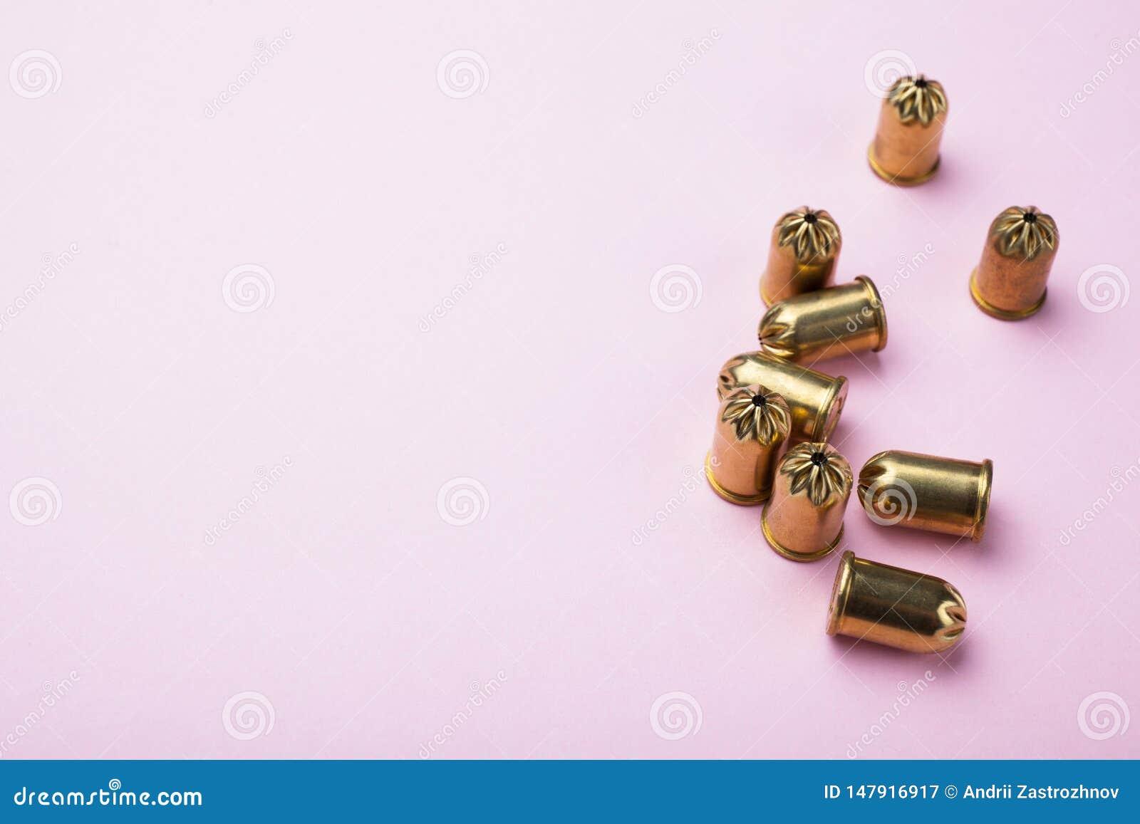 Pallottole d annata dell oro su un fondo rosa, spazio per testo