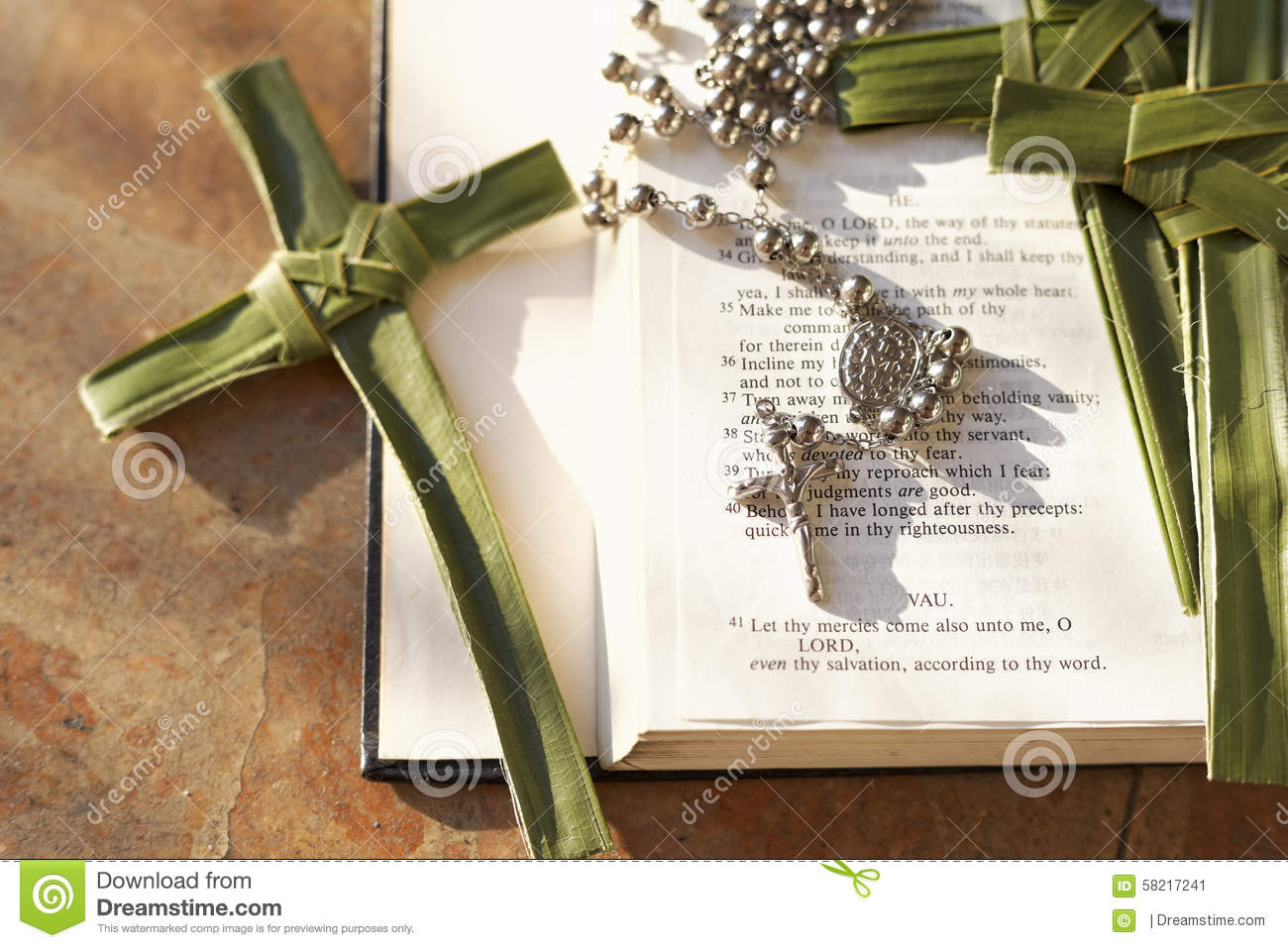 palm cross rosary beads sitting on an open bible stock photo
