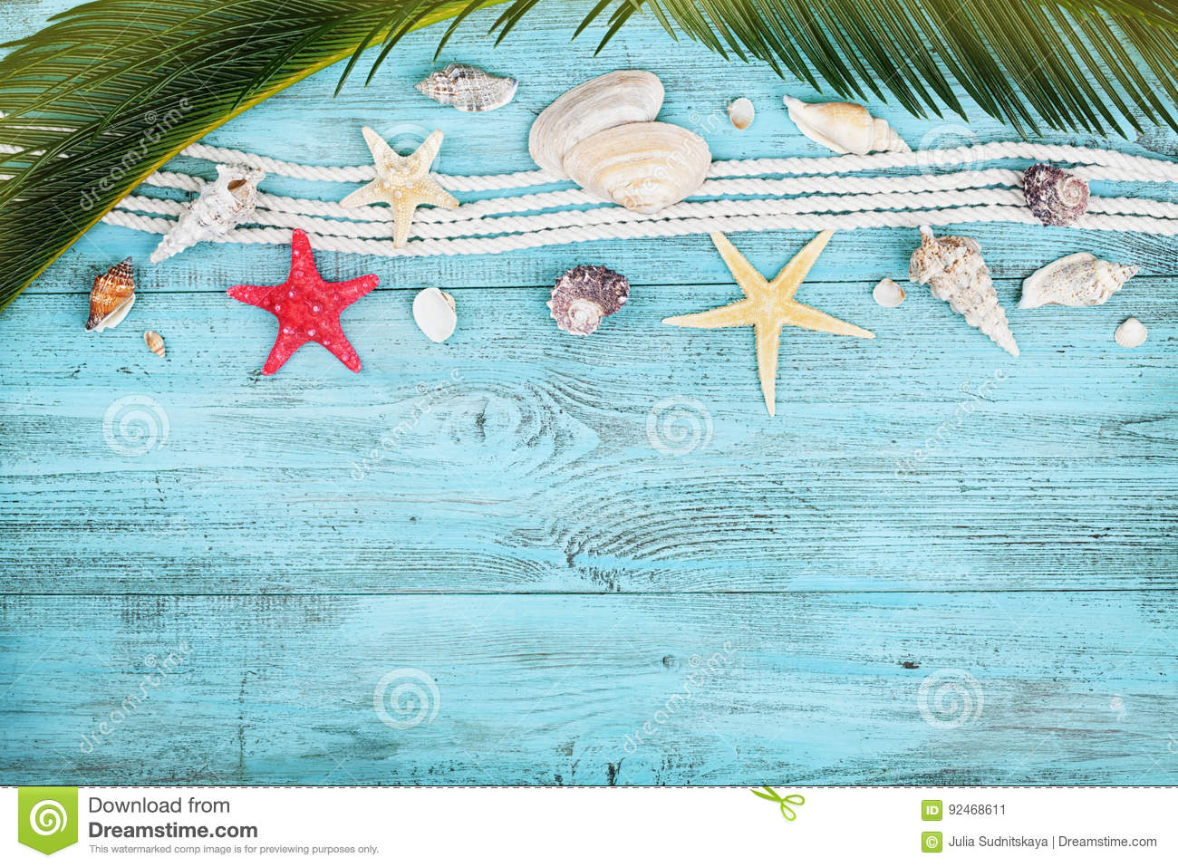 Palm leaves, rope, seashell and starfish on blue wooden table top view in flat lay style. Summer holidays, travel and vacation.