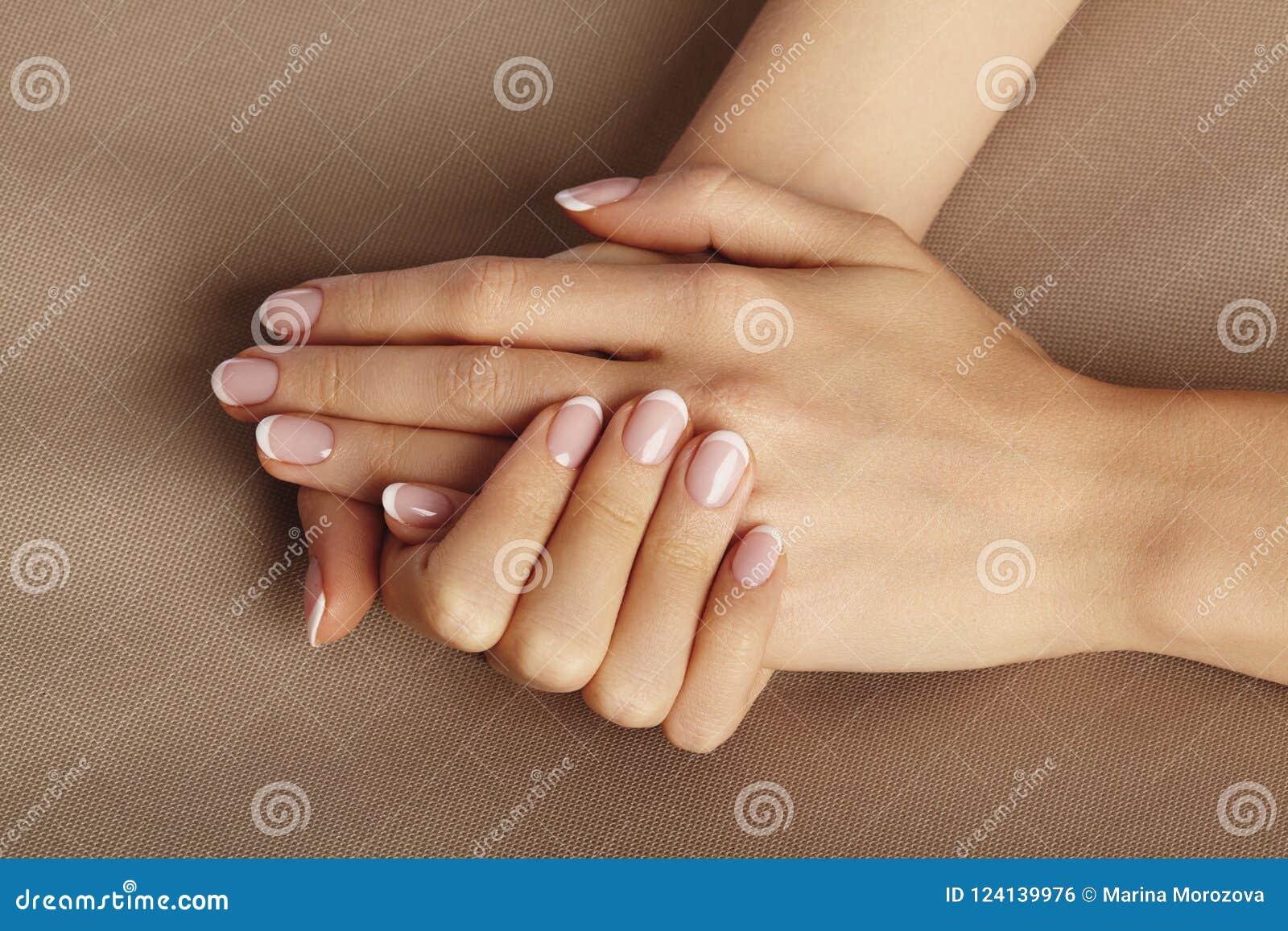 Palma femenina joven Manicura hermosa del encanto Estilo francés Pulimento de clavo Cuide sobre las manos y los clavos, piel limp