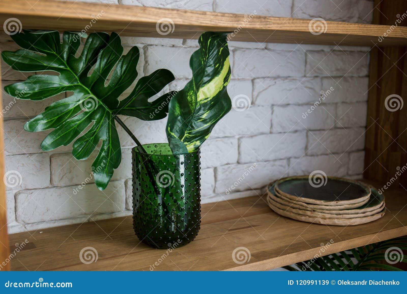 Palma liści stojak w zielonej wazie na drewnianej półce