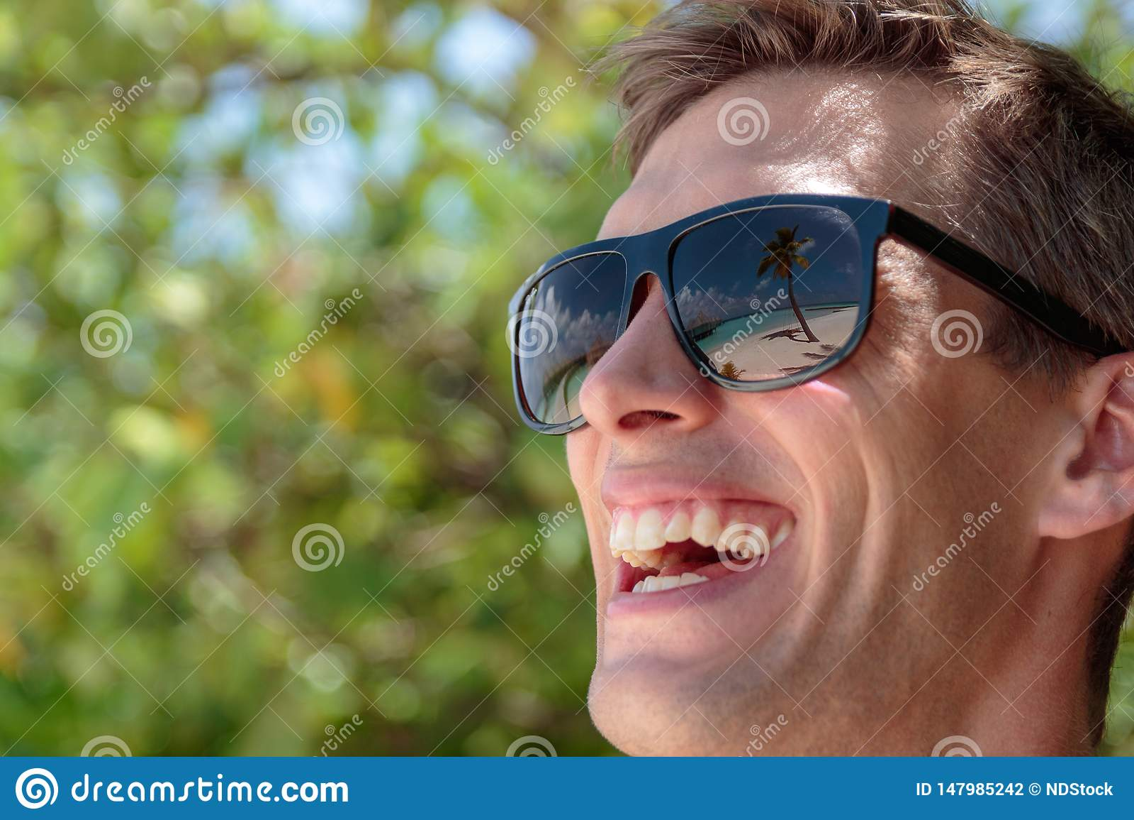 Palma, spiaggia bianca ed acqua blu cristallina riflesse negli occhiali da sole di un uomo felice maldives