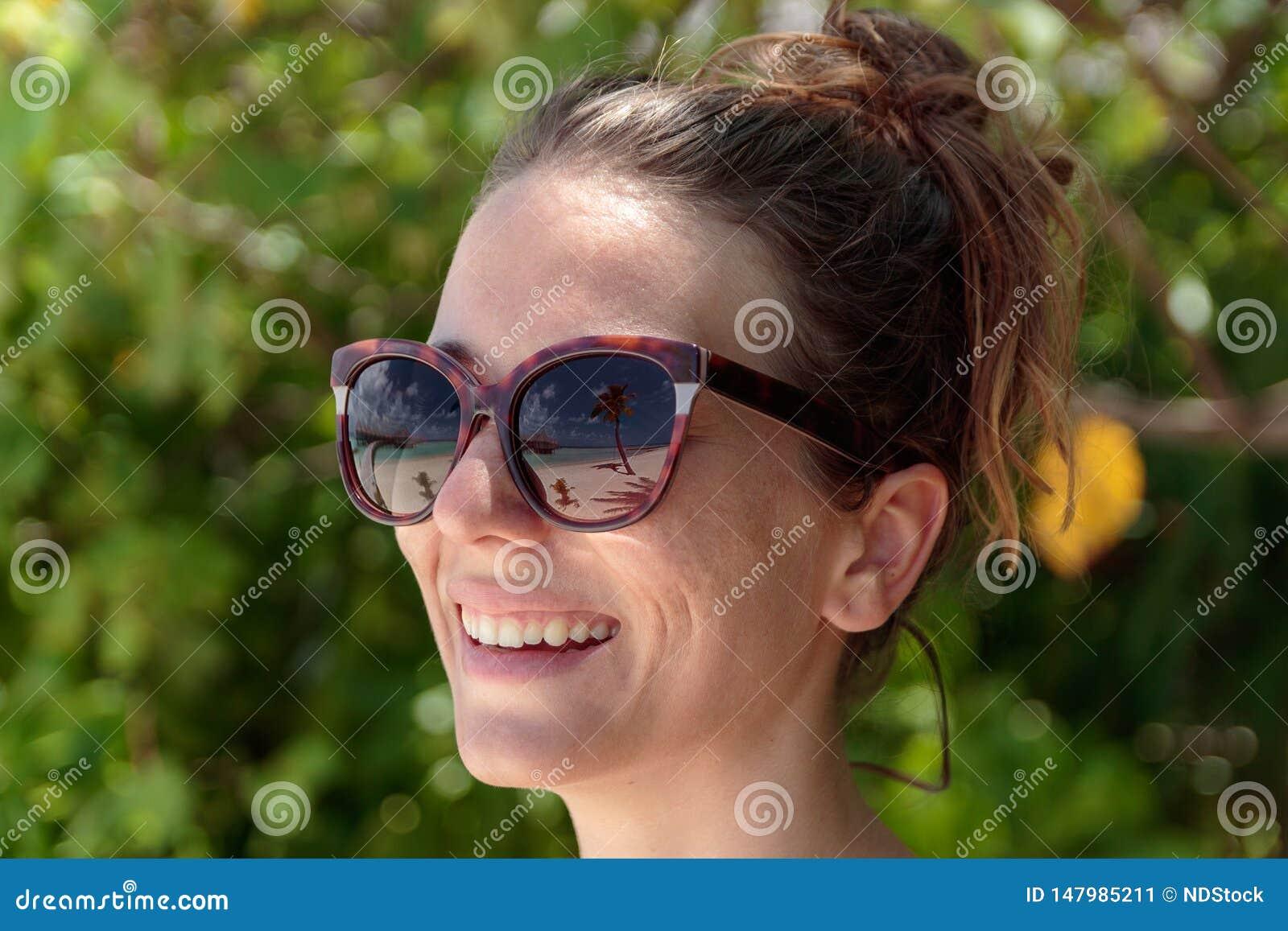 Palma, spiaggia bianca ed acqua blu cristallina riflesse negli occhiali da sole di una donna felice maldives