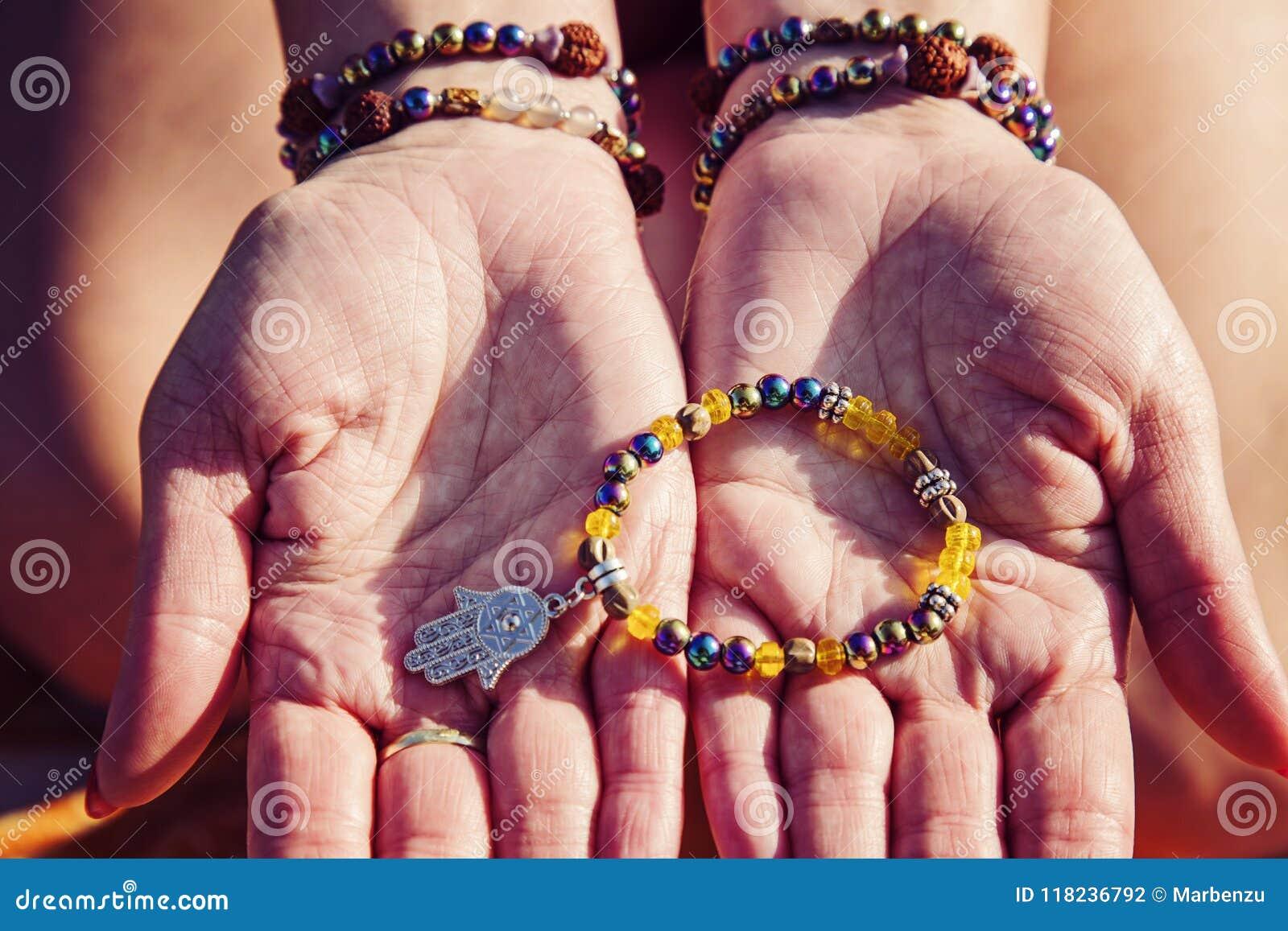 Palmas femeninas con las pulseras naturales de la gota que sostienen la pulsera con el colgante del hamsa