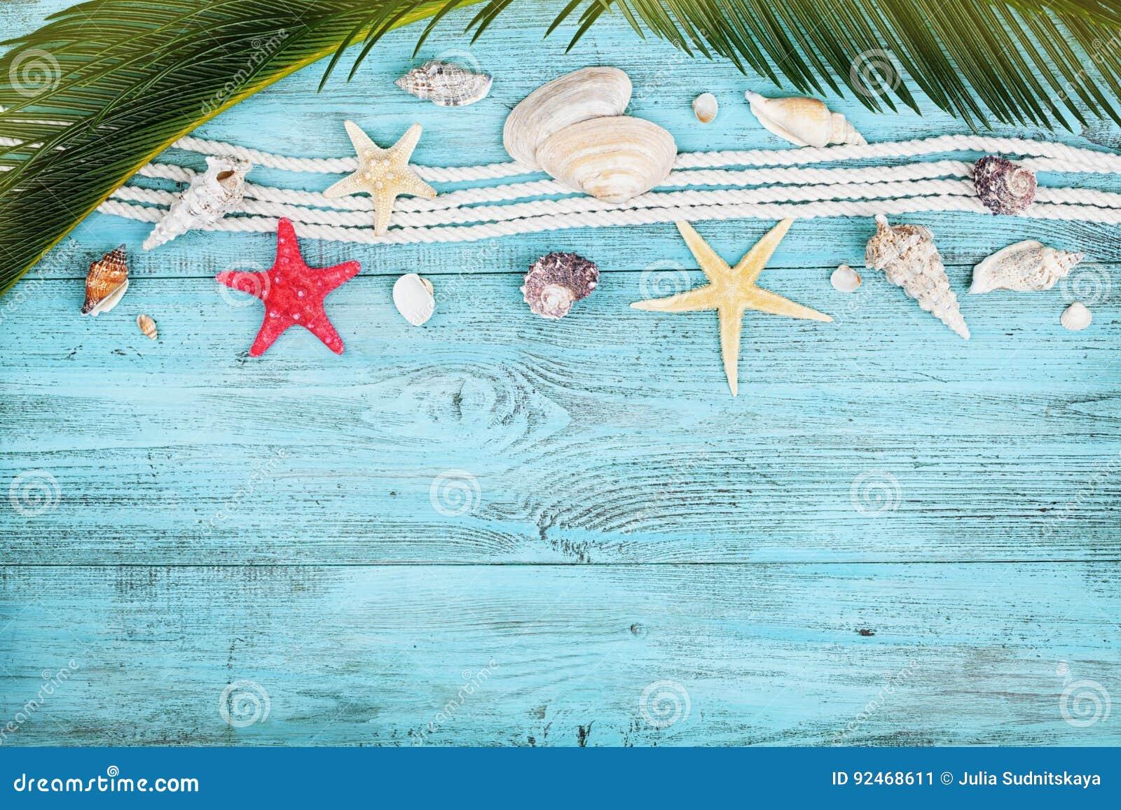 Palmblätter, Seil, Muschel und Starfish auf blauer Draufsicht des Holztischs in der Ebene legen Art Sommerferien, Reise und Ferie