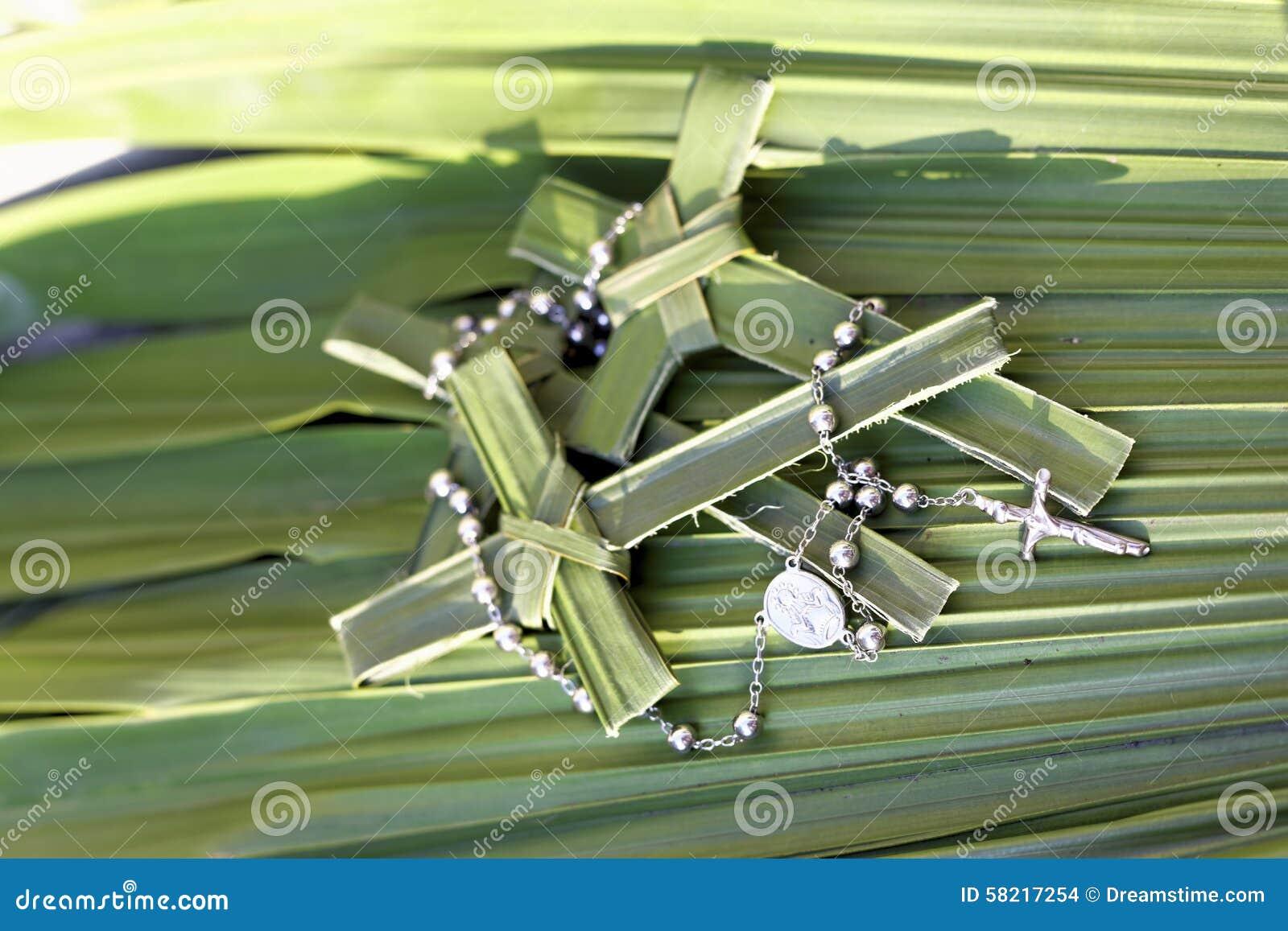 Palmenkreuze und -Rosenkranzperlen auf Palmblättern