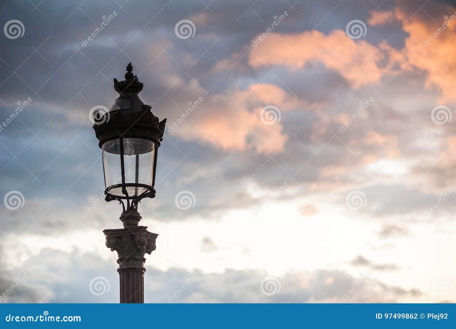 Palo della luce parigino contro le nuvole al tramonto