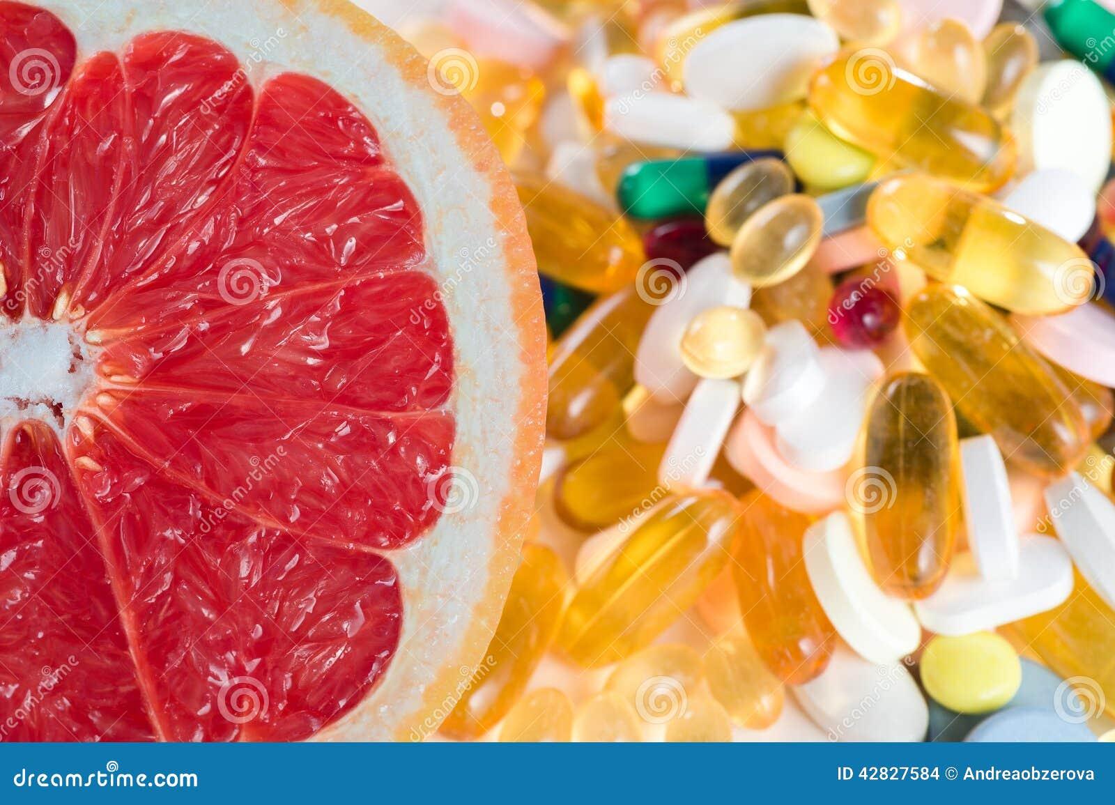 Pamplemousses et pilules, suppléments de vitamine sur le fond blanc, concept d alimentation saine