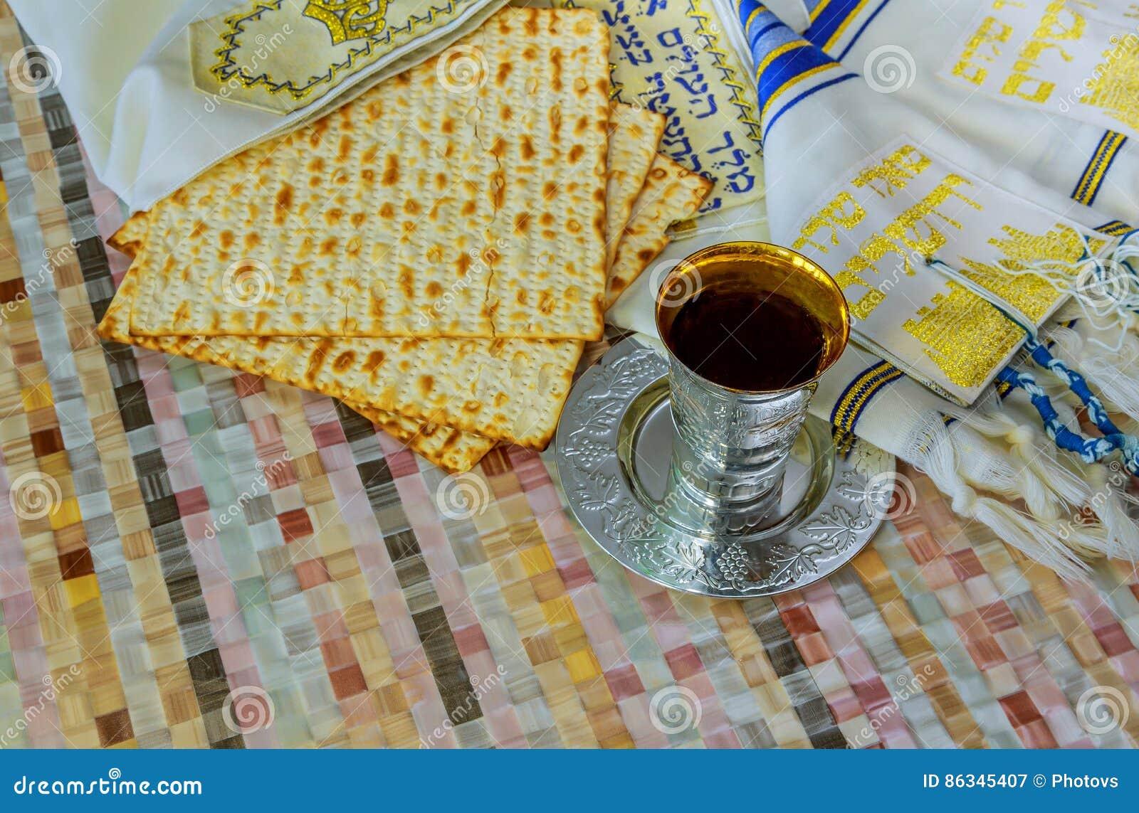 Pan ácimo de la pascua judía tradicional judía y una taza del vino con el texto de la bendición tradicional del vino