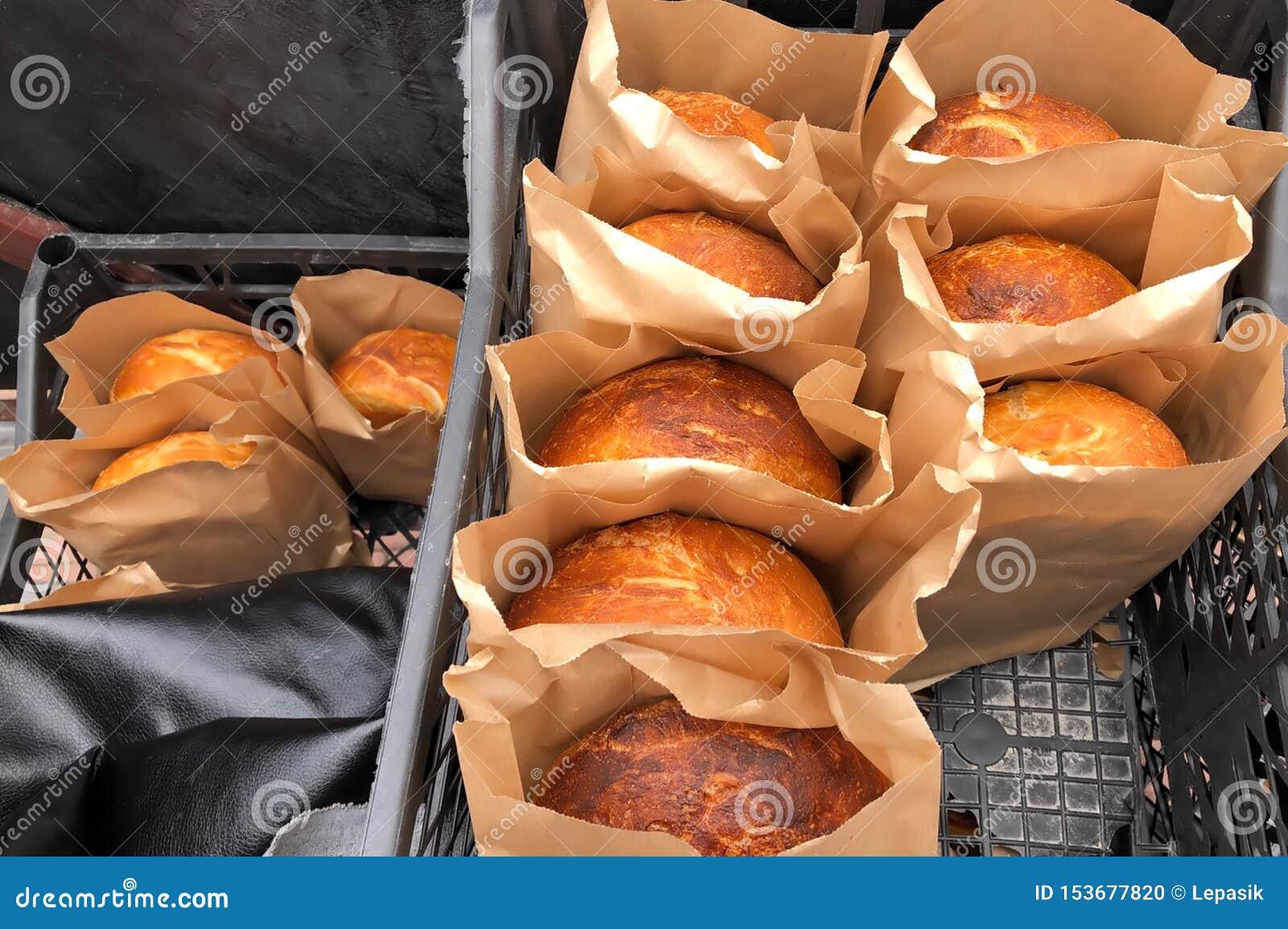 Pan cocido hecho en casa en el papel que empaqueta, productos de la panadería de hombres de negocios privados