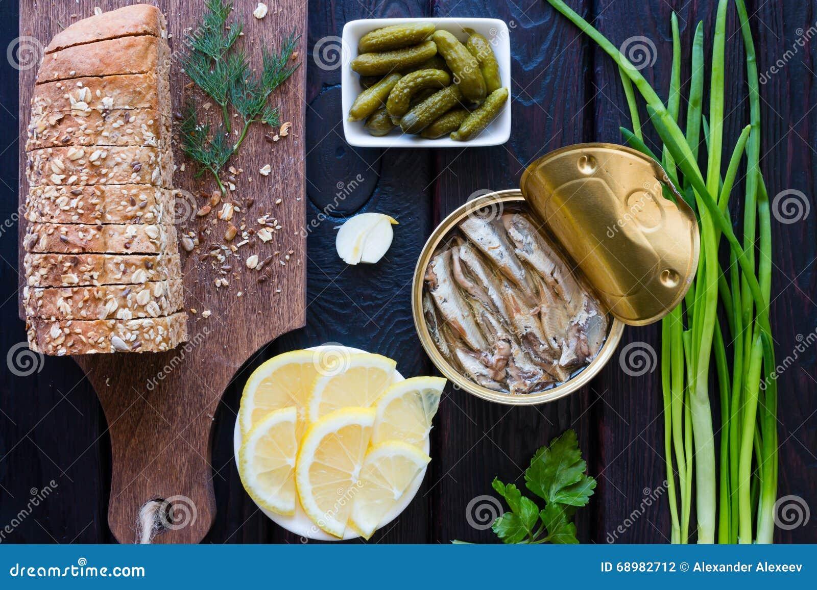 Pan con los granos, los pepinillos conservados en vinagre, el limón y los espadines en un negro