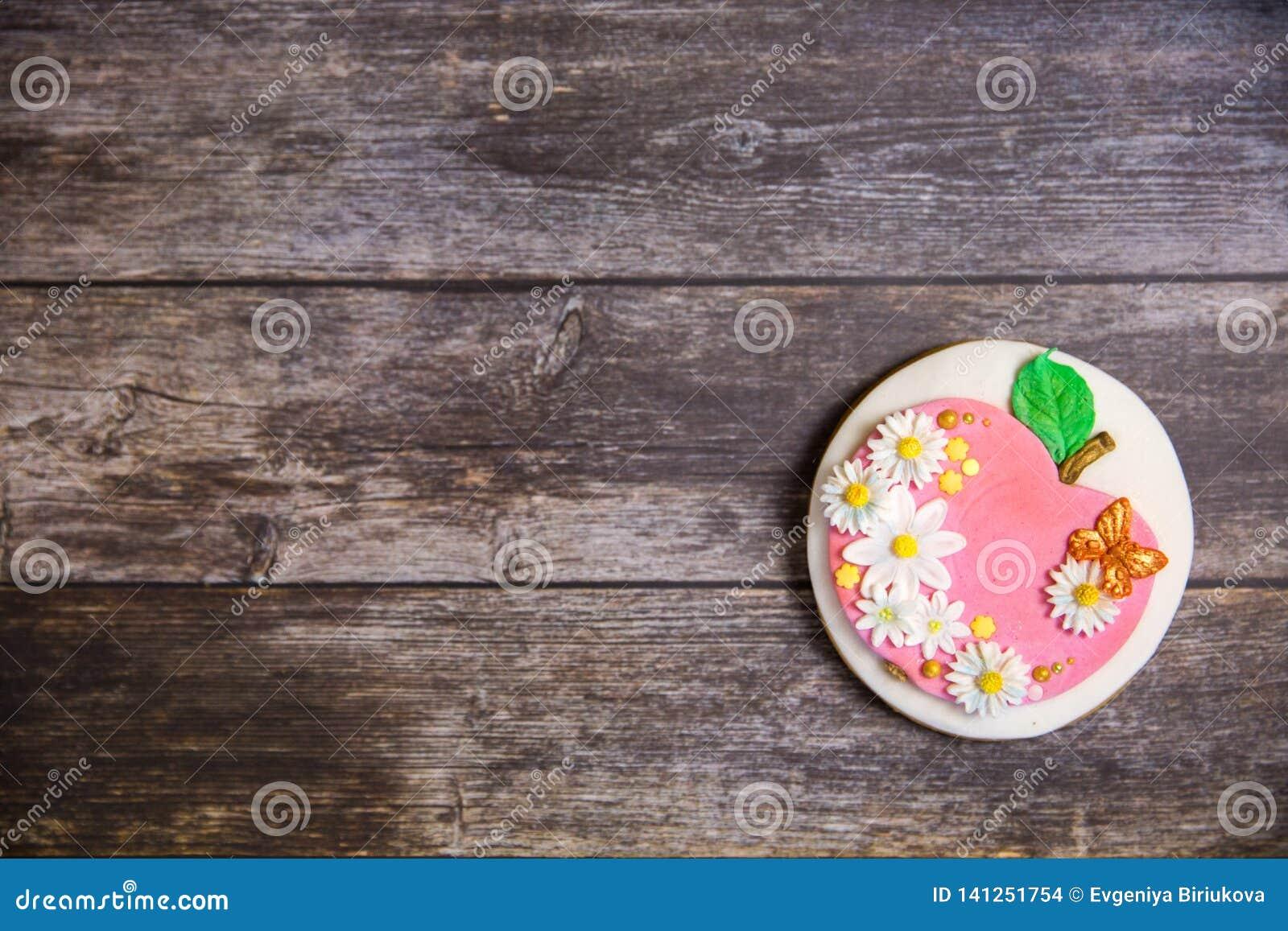 Pan di zenzero dipinto a mano rotondo su fondo di legno Disposizione piana Apple con i fiori e le farfalle Copi lo spazio Dessert