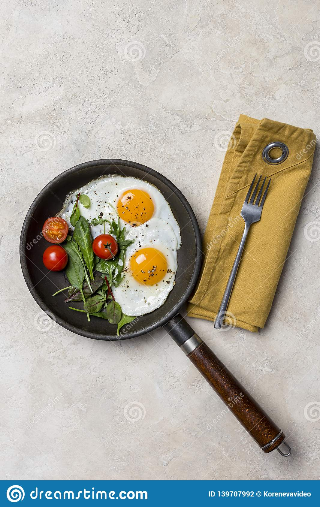 Pan and fried eggs for breakfast with herbs at beige background