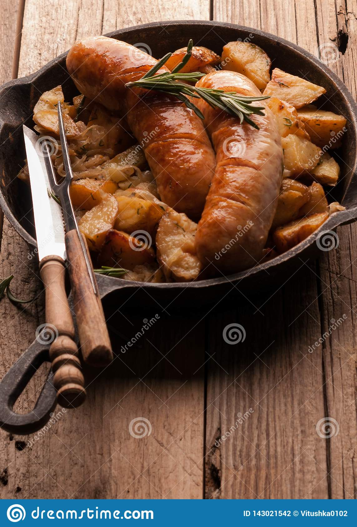 Pan with fried potatoes and grilled sausages, green rosemary, fork and knife
