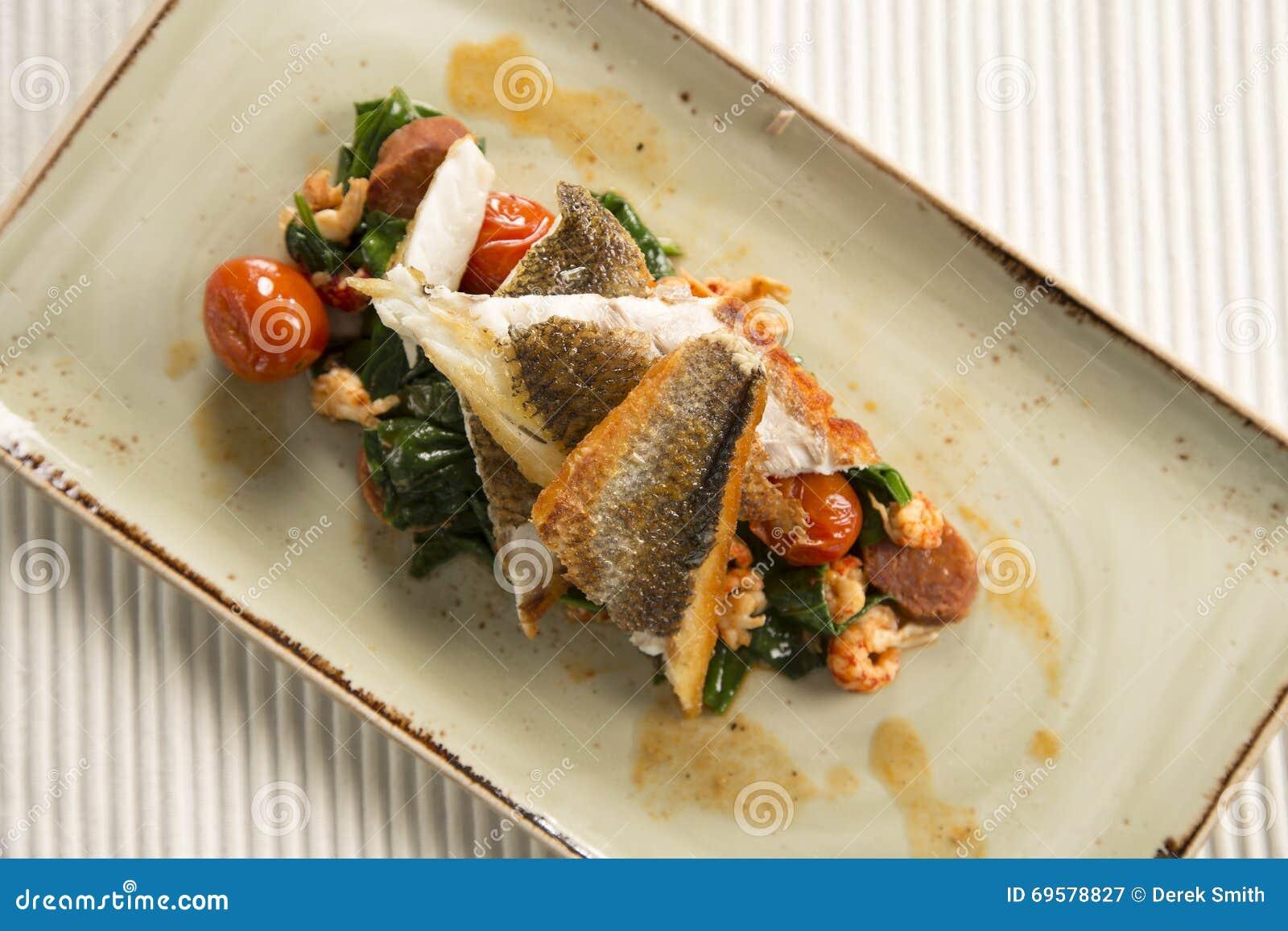 Pan fried sea bass with crayfish, chorizo, baby spinach & cherry tomatoes