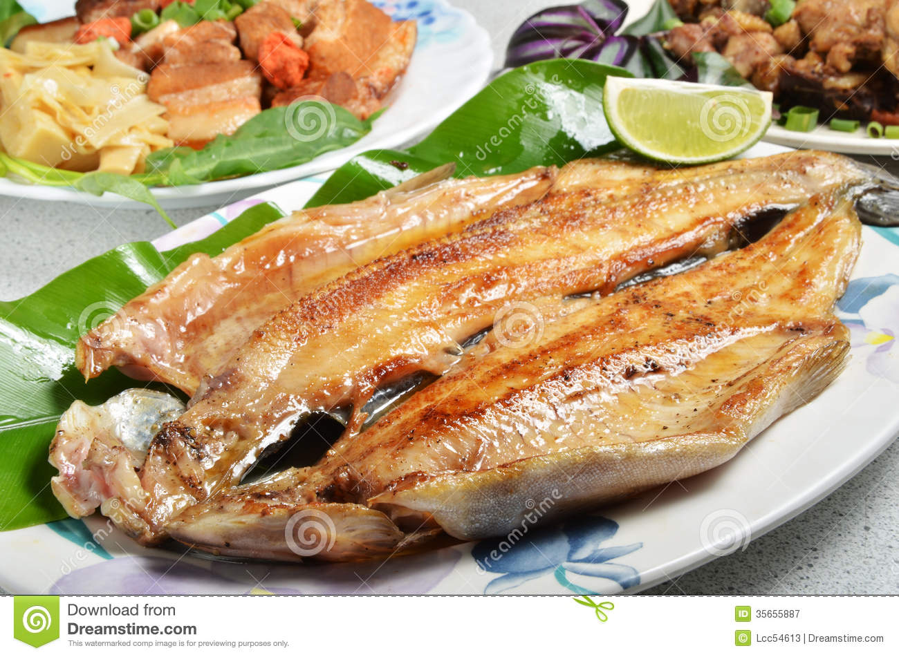 Pan fried trout with lemon on plate.