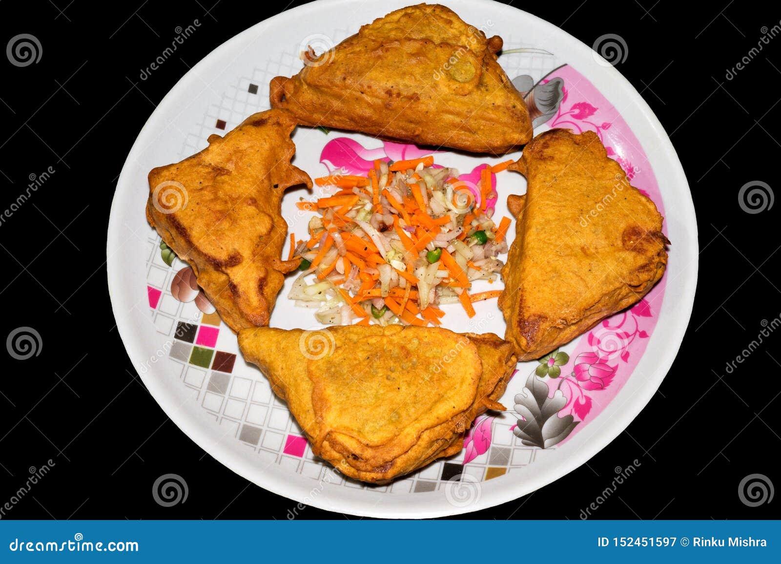 Pan Pakora de la forma del triángulo en una placa en fondo negro con la ensalada cortada