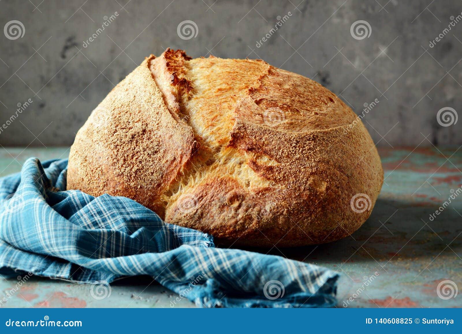 Pan recientemente cocido hecho en casa del país hecho de trigo y de harina entera del grano en un fondo gris-azul