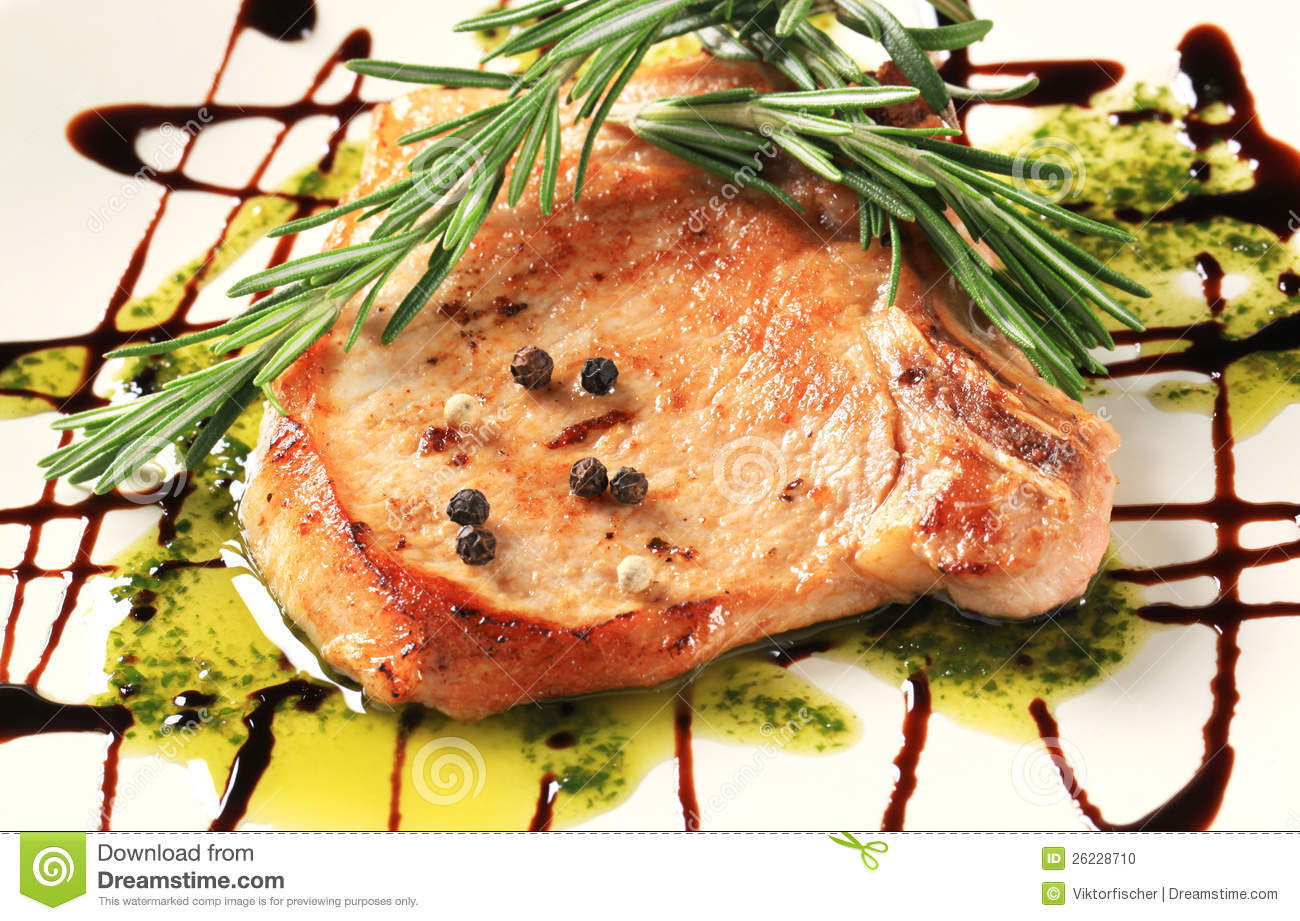 Pan-roasted pork chop decorated with rosemary and balsamico.