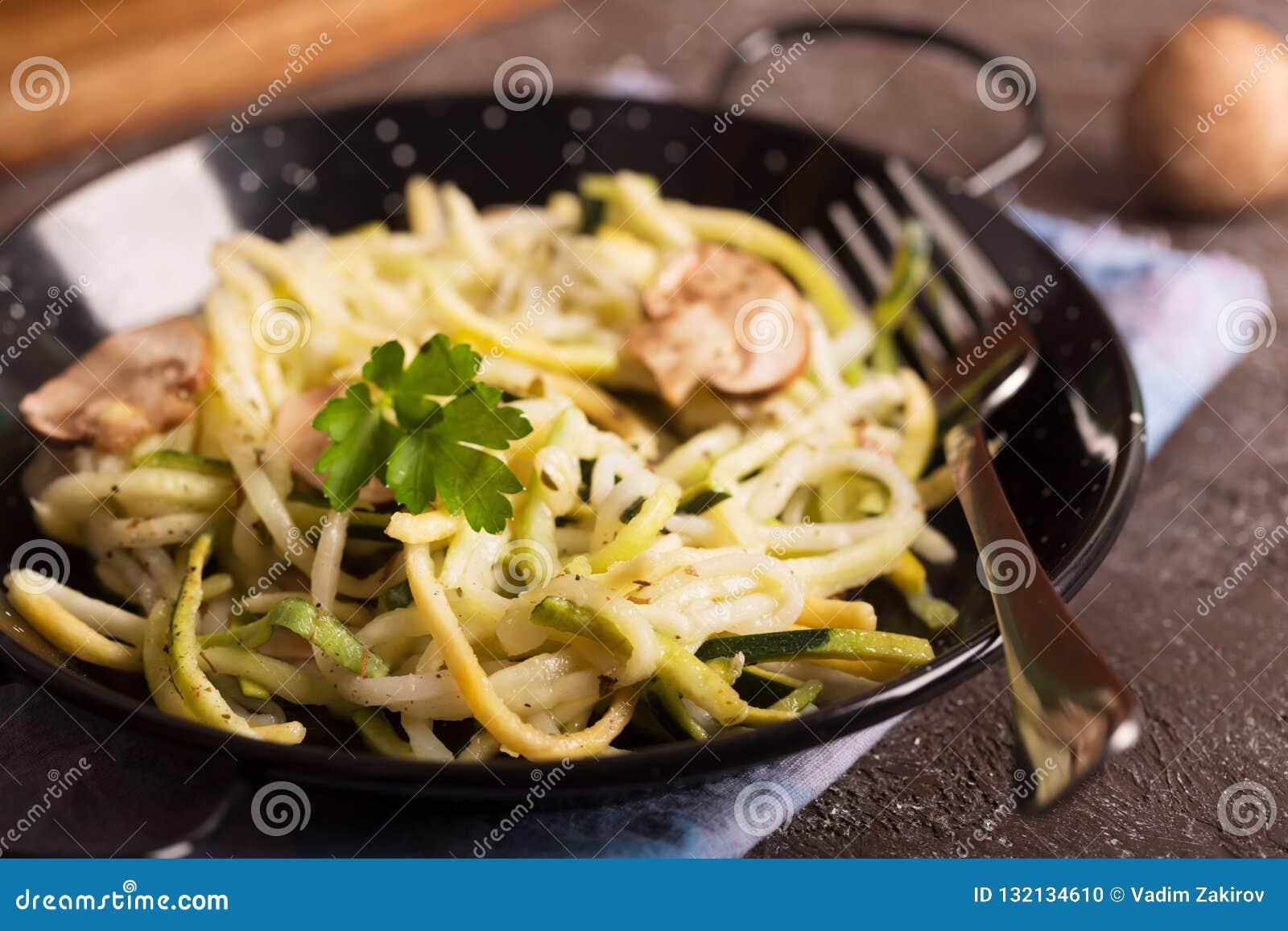 Pan van spaghetti van courgette en paddestoelsaus op houten lijst wordt voorbereid die