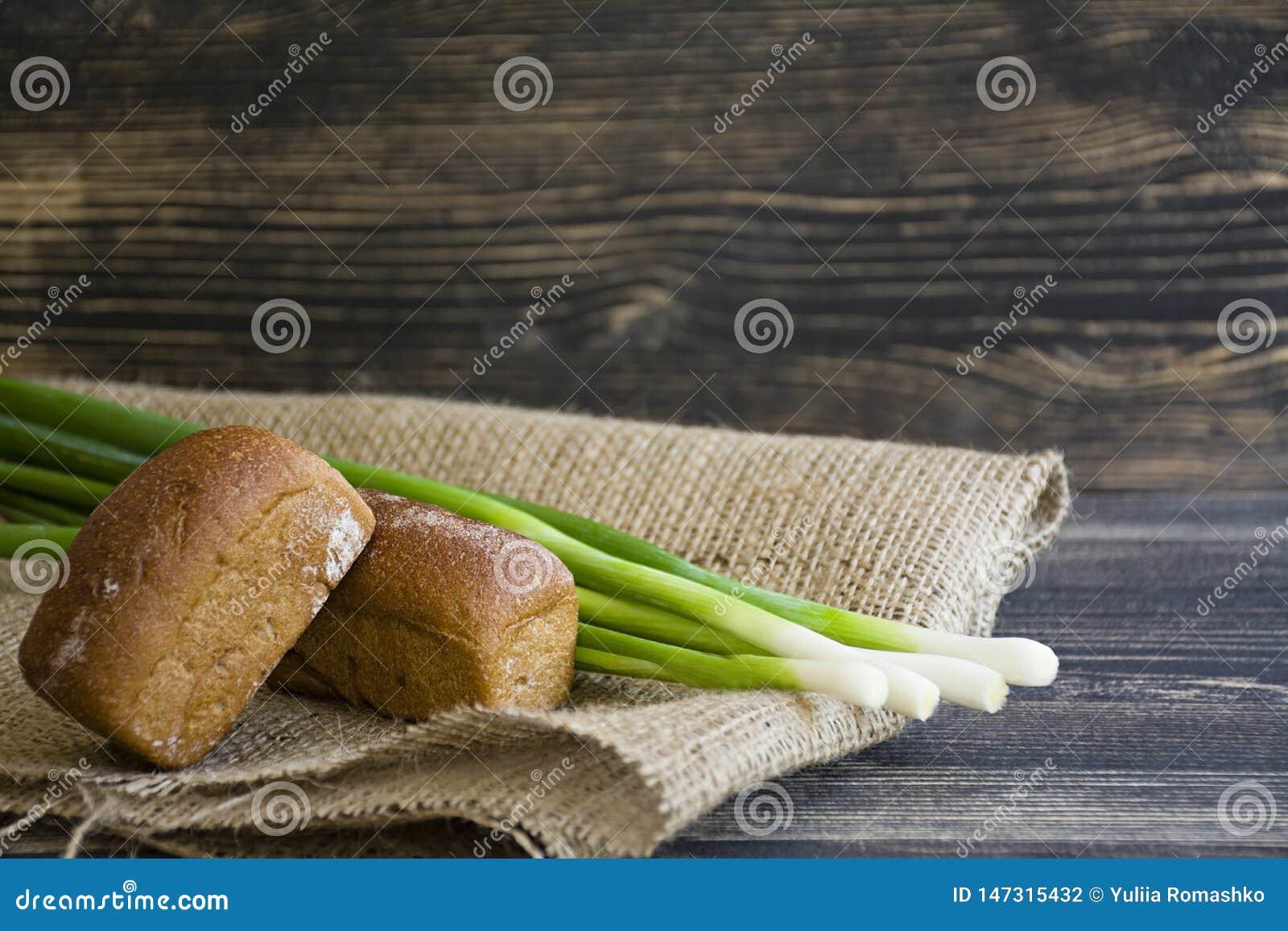 Pan y cebolla verde recientemente cocidos en un fondo de madera oscuro
