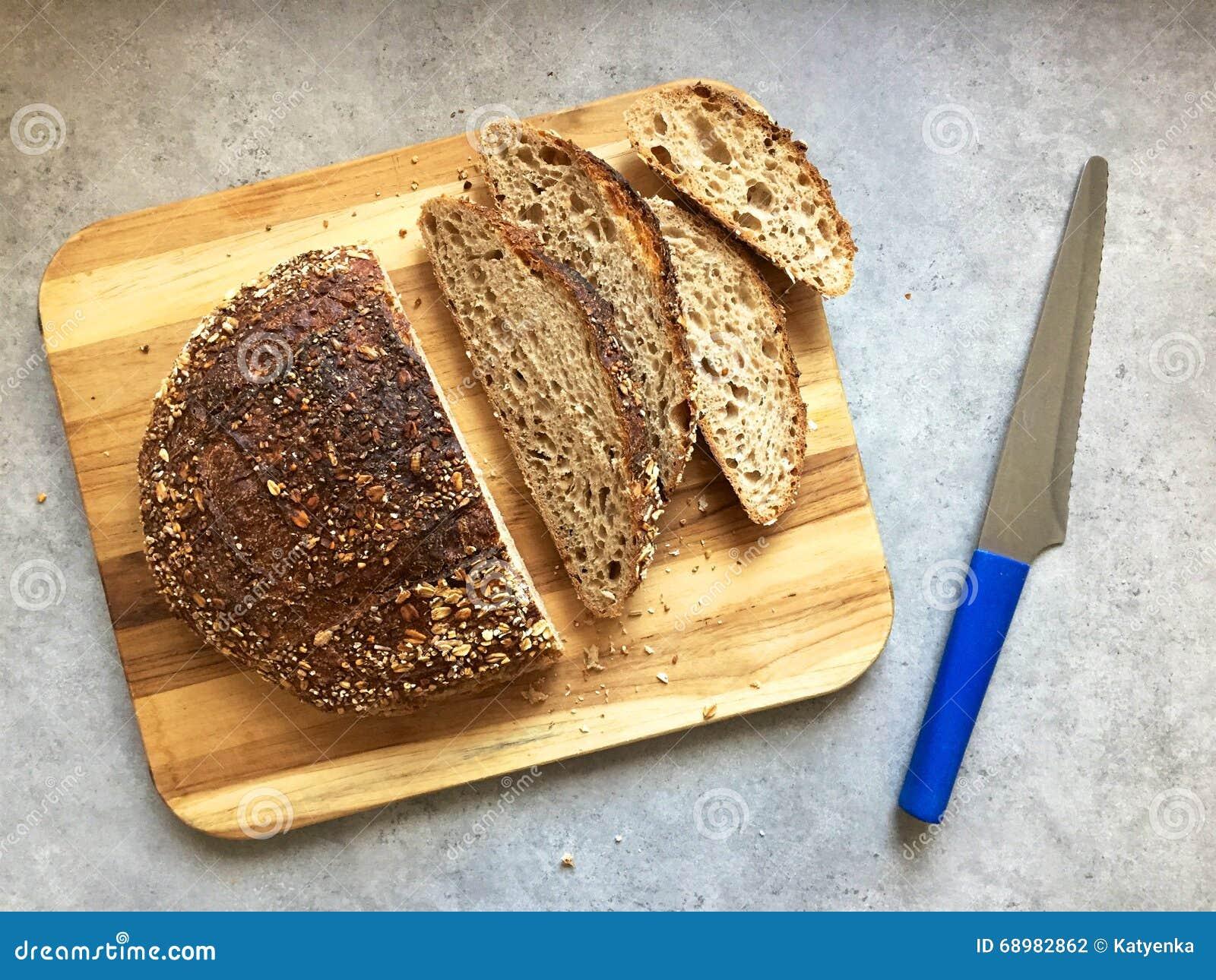 Pan y rebanadas artesanales del pan del pan amargo en tabla de cortar de madera