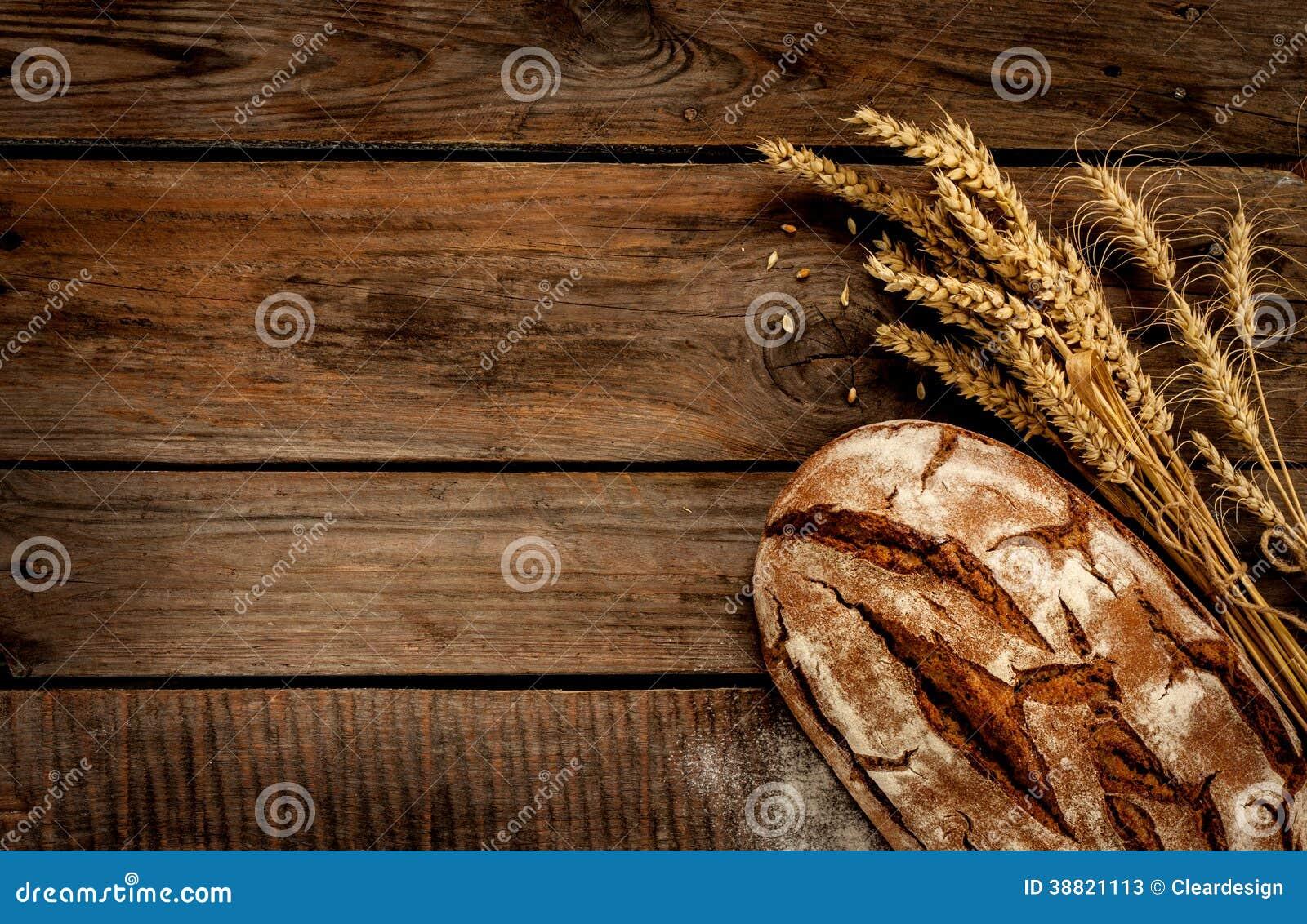 Pan y trigo rústicos en la tabla de madera del vintage