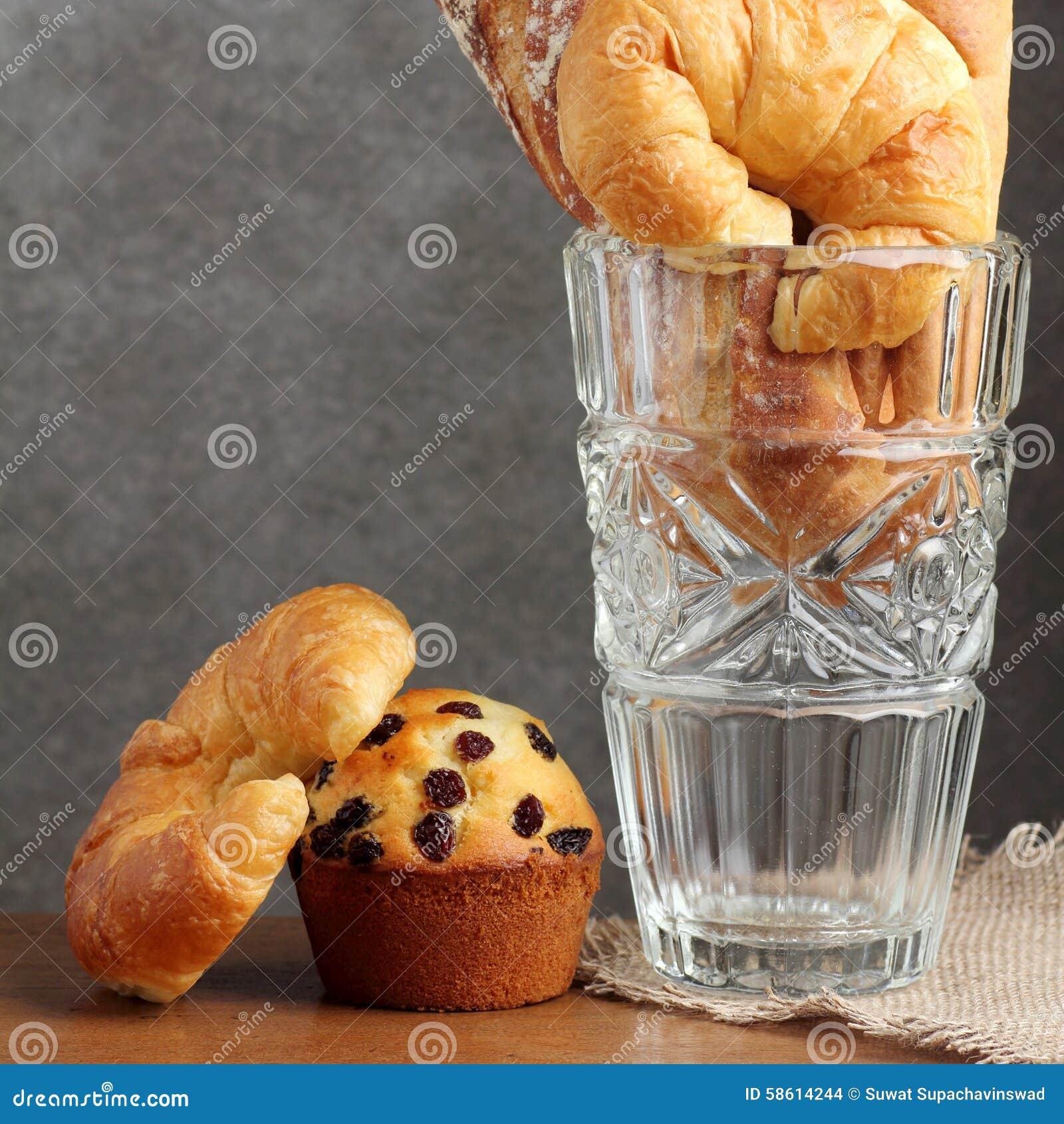 Panadería del mollete del clavito del cruasán en el soplo de cristal en la tabla del teakwood