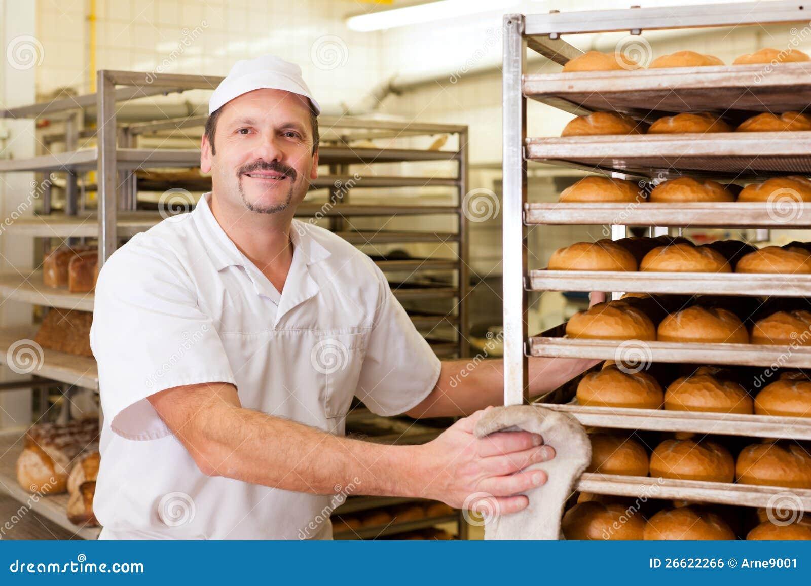 Panadero en su pan de la hornada de la panadería