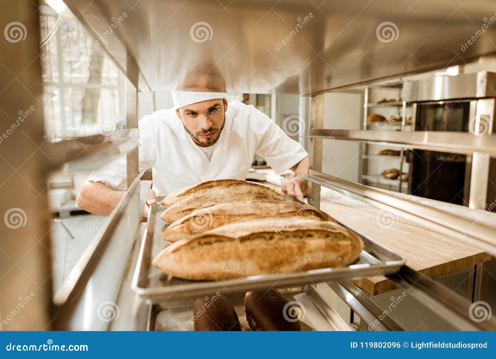 Panadero profesional que pone las bandejas de pan fresco en soporte