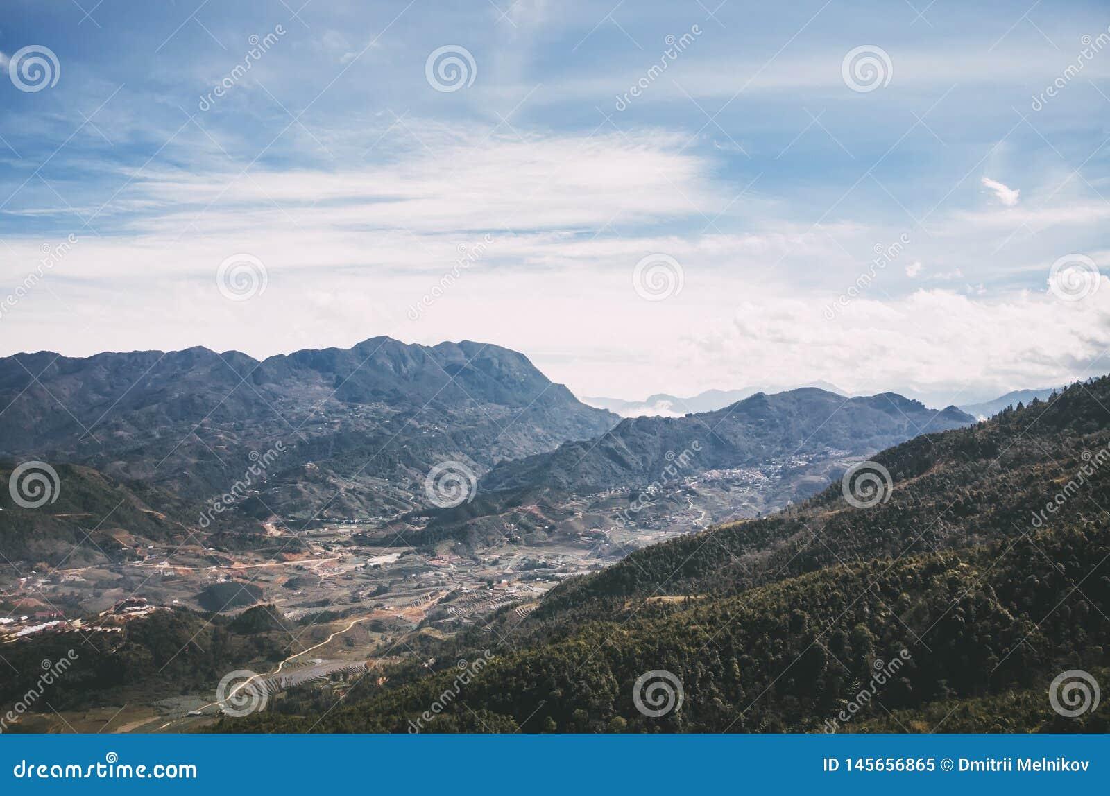 Panaromic e ideia bonita das casas e de campos verdes do arroz do terraço com céu azul e nuvens na vila em Sapa