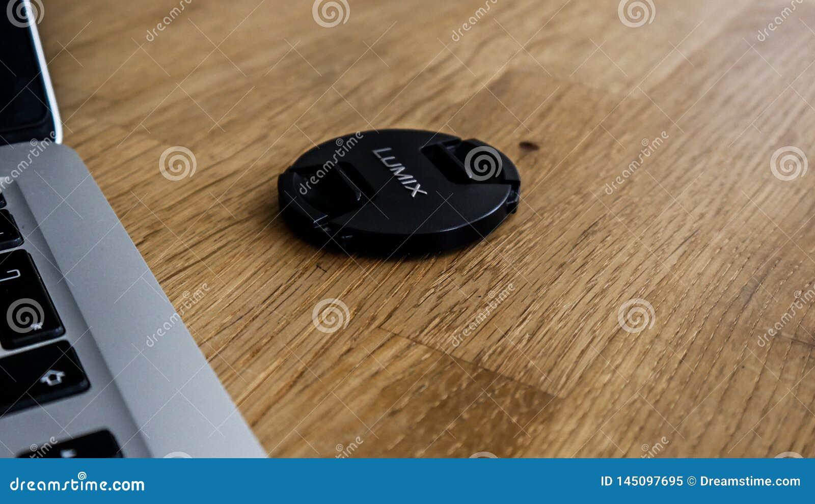 A panasonic lumix lens cap next to a macbook