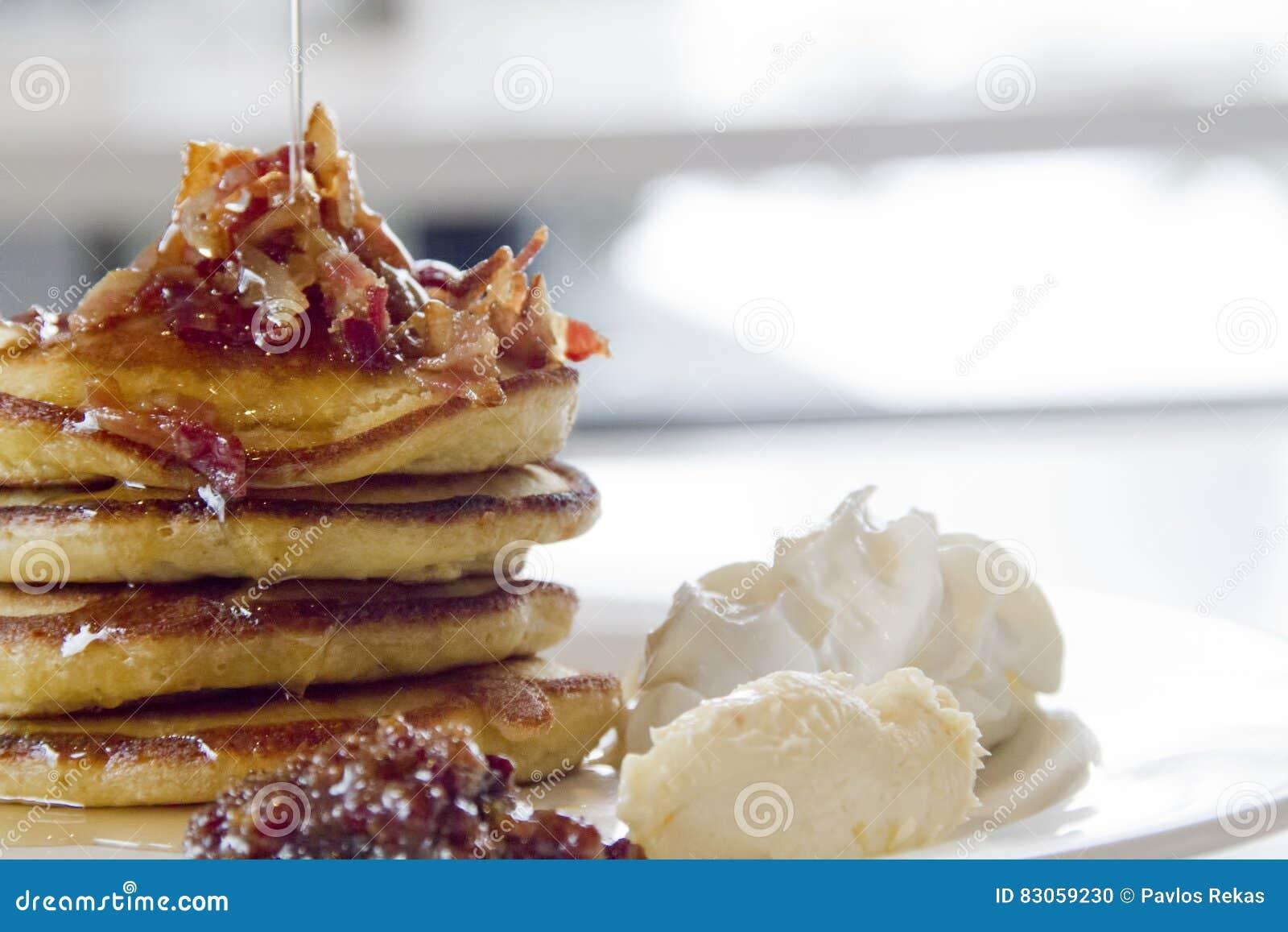 Pancake gastronomici della prima colazione con i pezzi del bacon