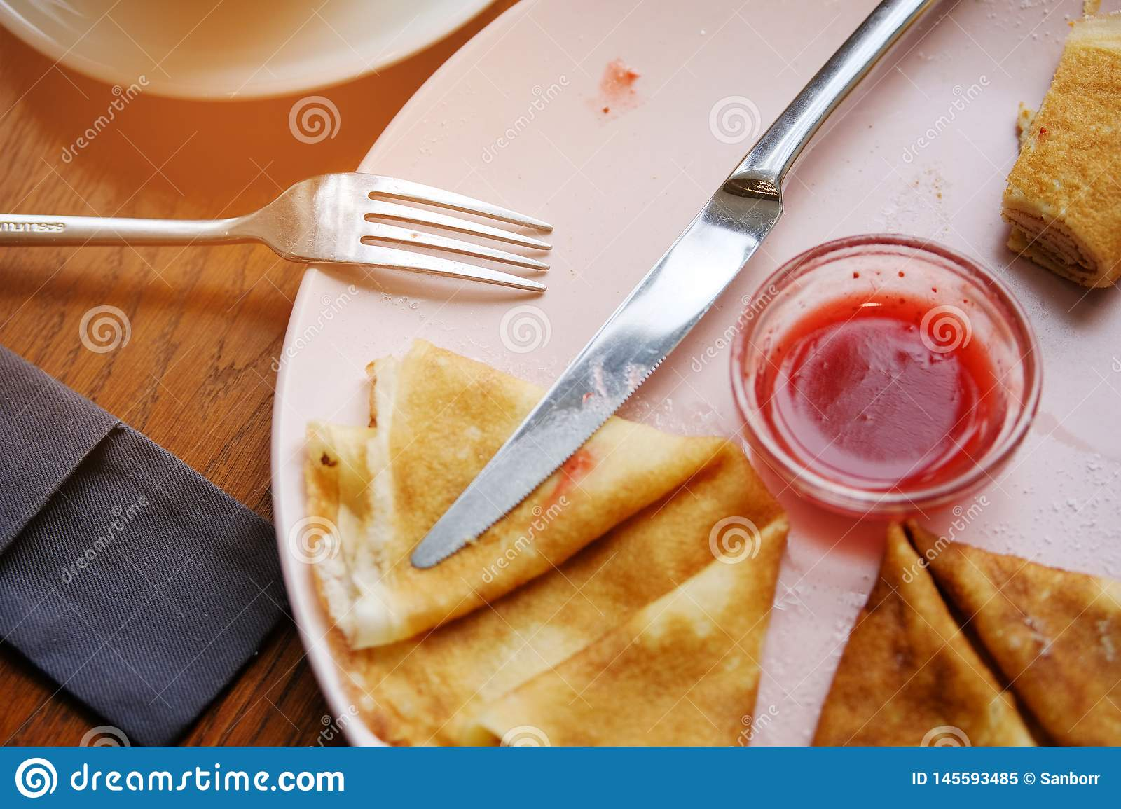Pancakes with berry jam on a white plate on a wooden background. Near a fork and knife. The concept of food.