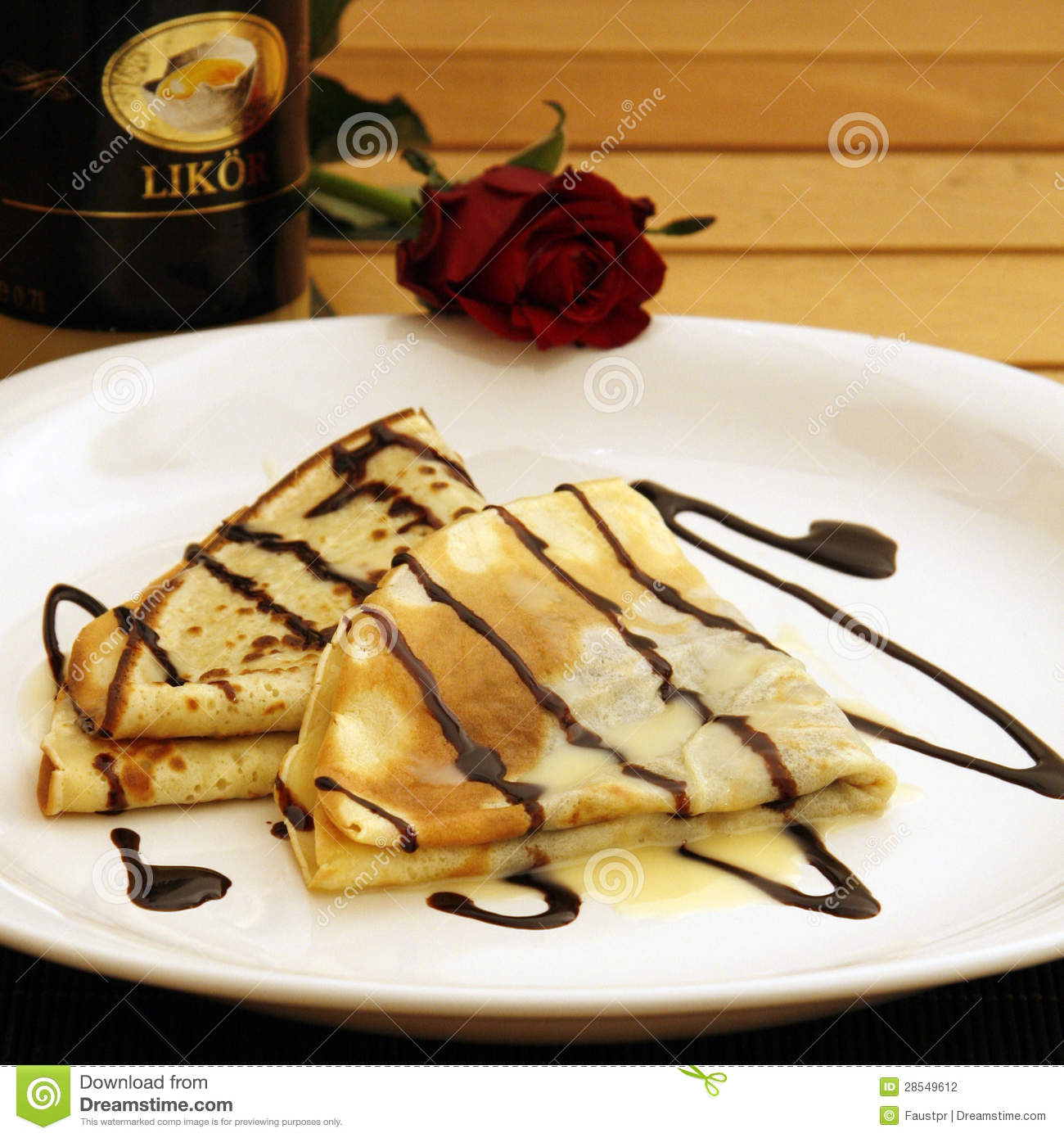 Pancakes with chocolate sauce and eggnog served on a plate with a rose ...