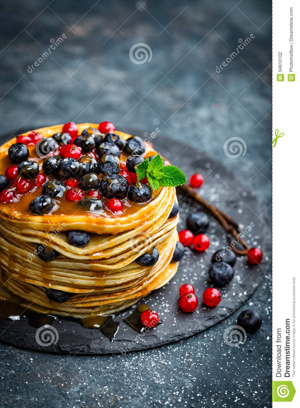 Pancakes with fresh berries and maple syrup on dark background