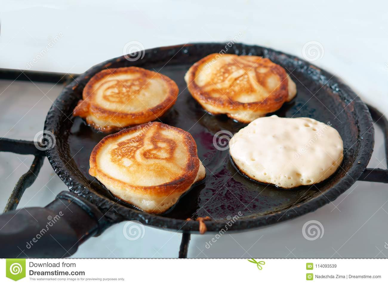Pancakes are fried in a frying pan, four pancakes are cooked in oil on a frying pan
