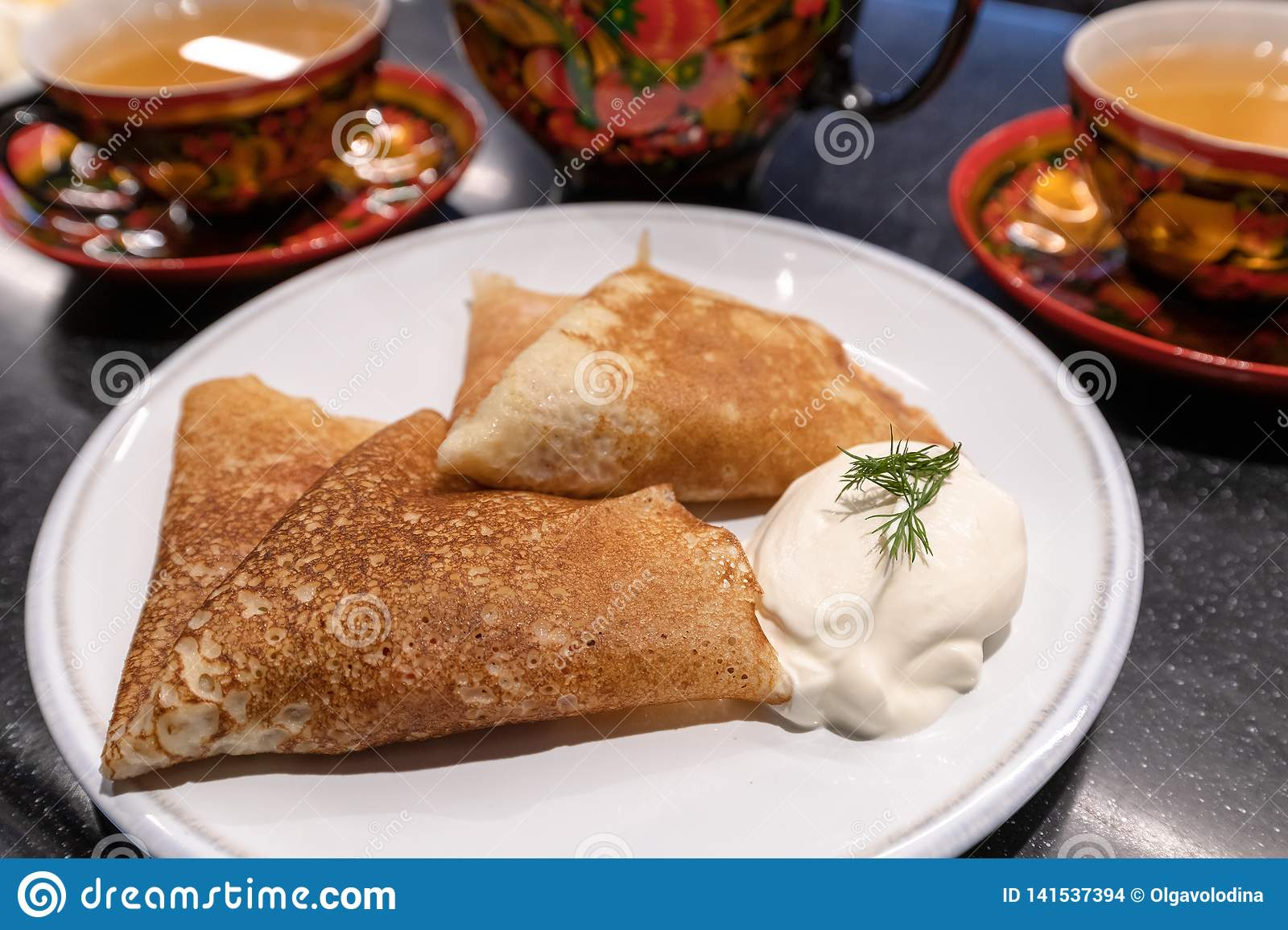 Pancakes with sour cream and tea in traditional dish for holiday Maslenitsa