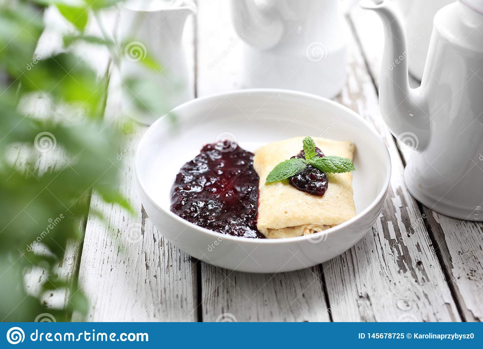 Pancakes stuffed with white cheese with dark fruit jam