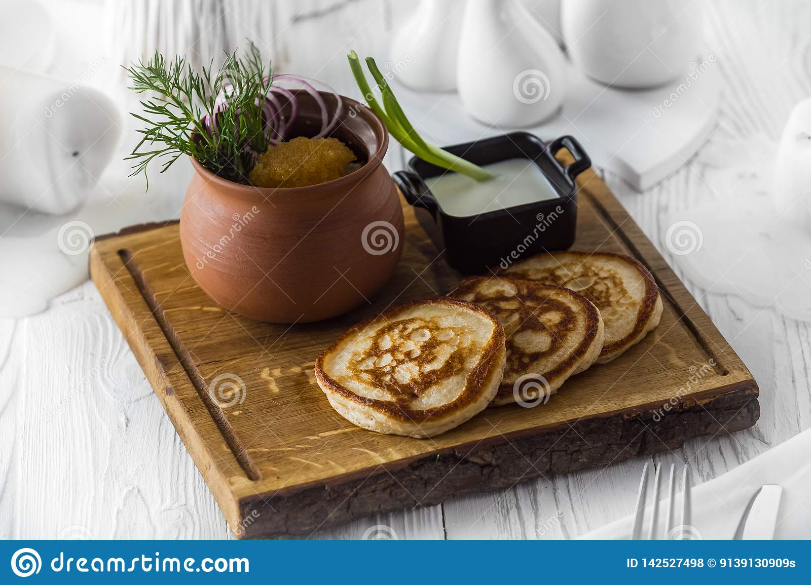 Pancakes with vegetables and dip sauce on a board