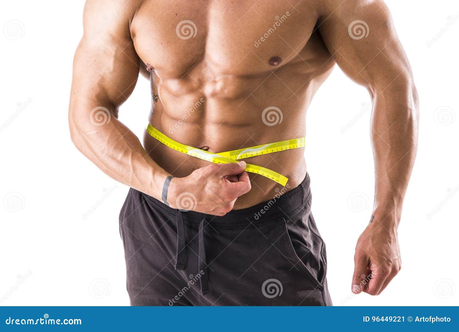 Pancia di misurazione dell uomo muscolare del culturista con la misura di nastro